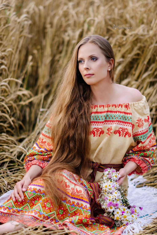 девушка в платье в русском стиле в сидит в пшеничном поле