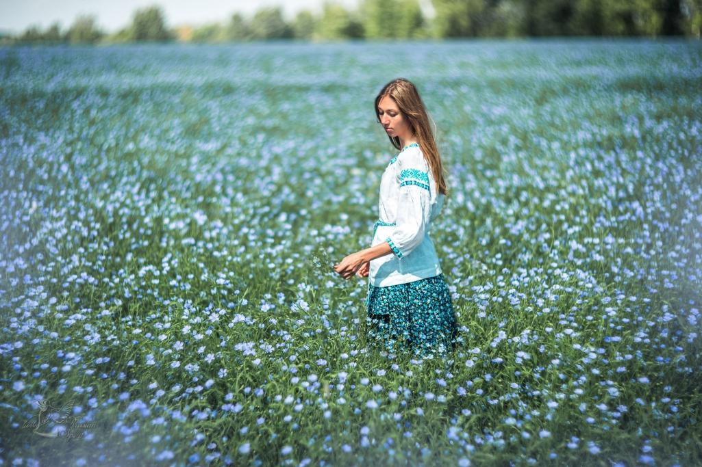 девочка в русском народном платье в цветущем поле льна