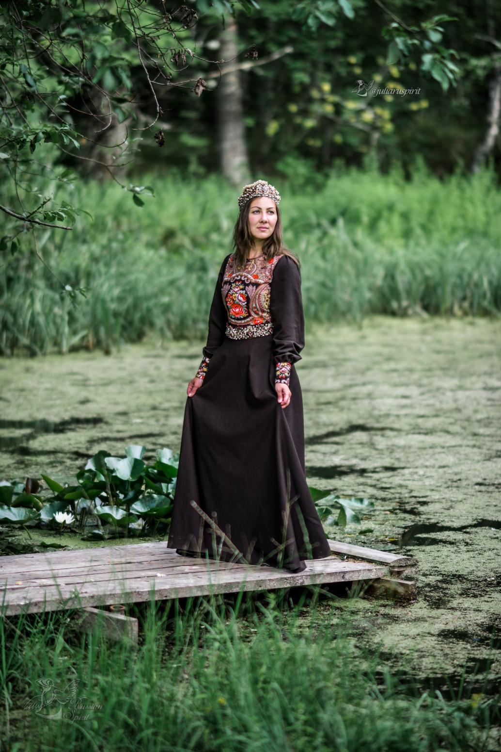 Девушка в костюме в русском стиле на мостике у пруда