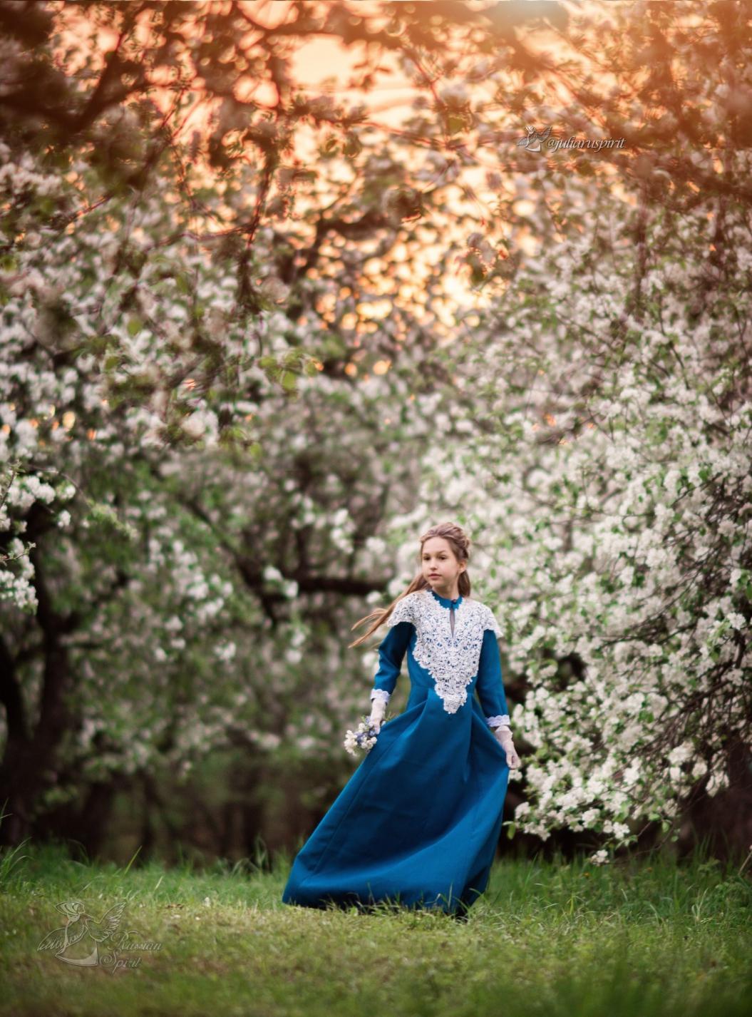 Девочка в синем винтажном платье в яблоневом саду