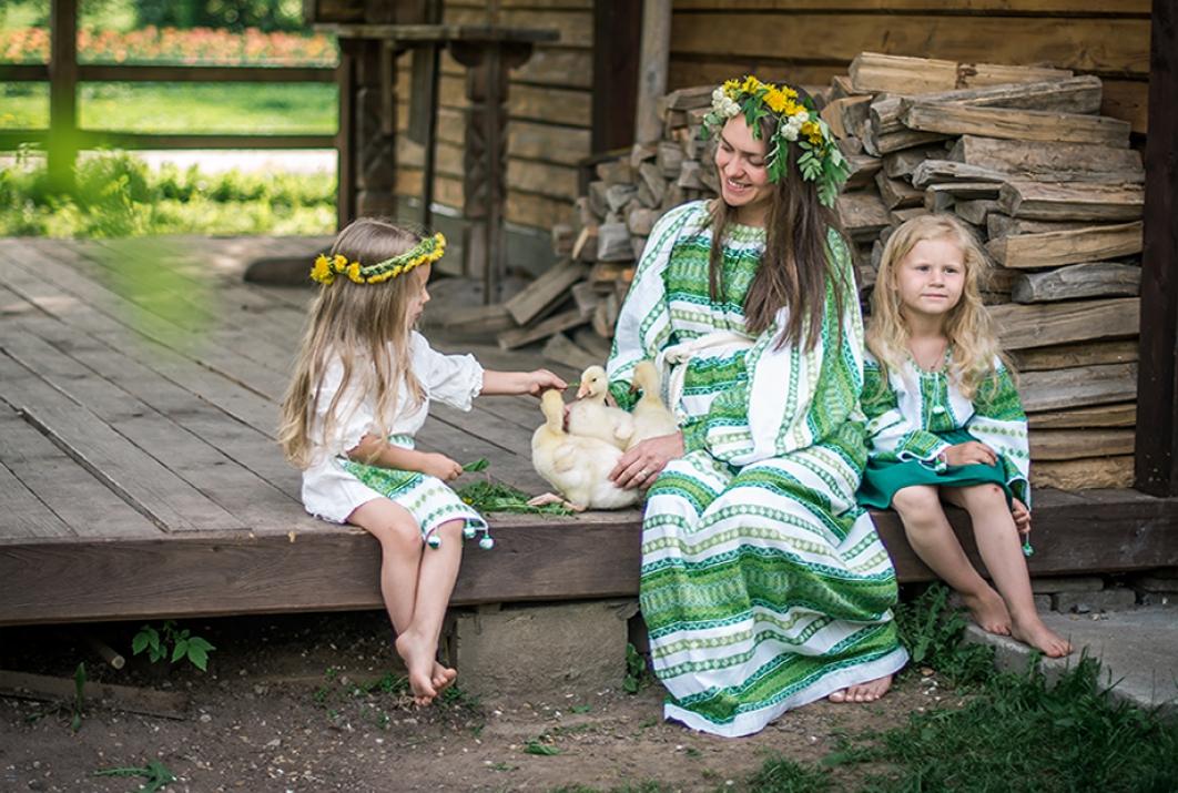 Мама с дочками в русских народных костюмах на крылечке с утятами