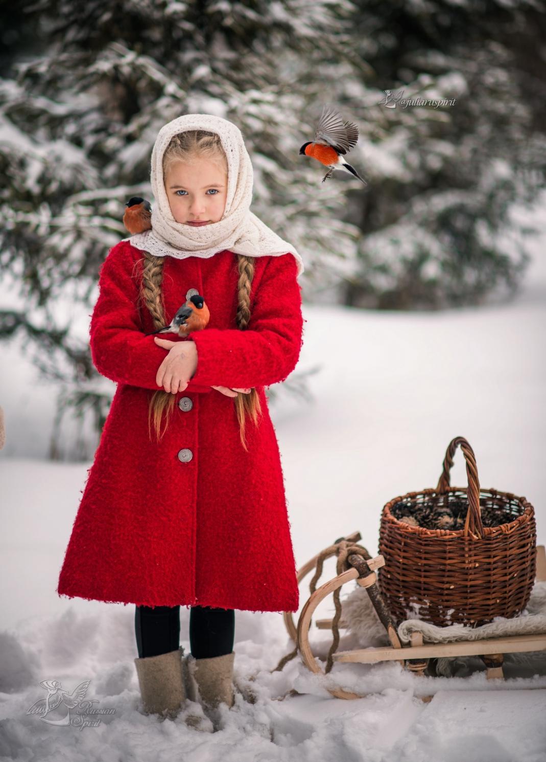 Девочка в красном пальтона фотосессии со снигирями