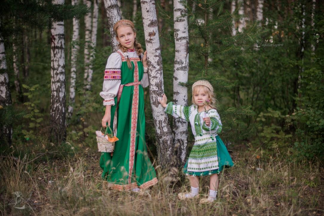 Сестрёнки в русских народных костюмах в лесу у берёзок с корзиной