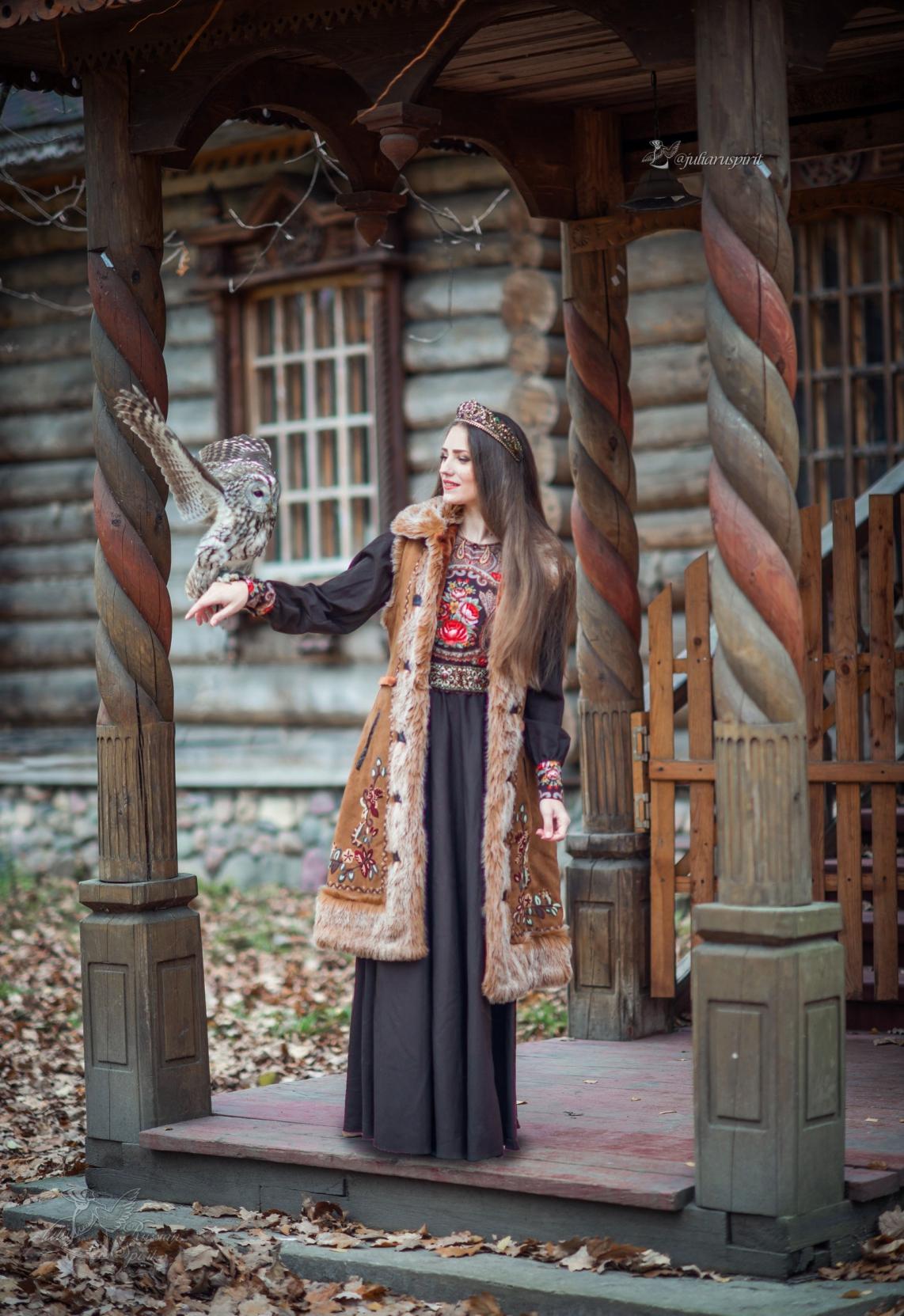 Девушка в коричневом платье в русском стиле и меховой жилетке с совой