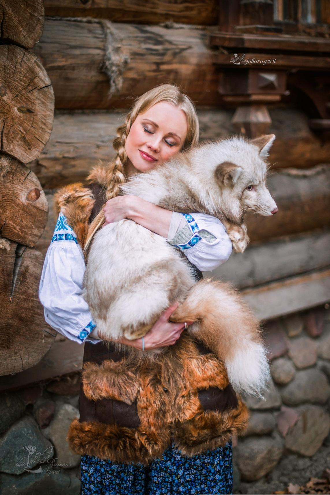 Девушка обнимает белую лису