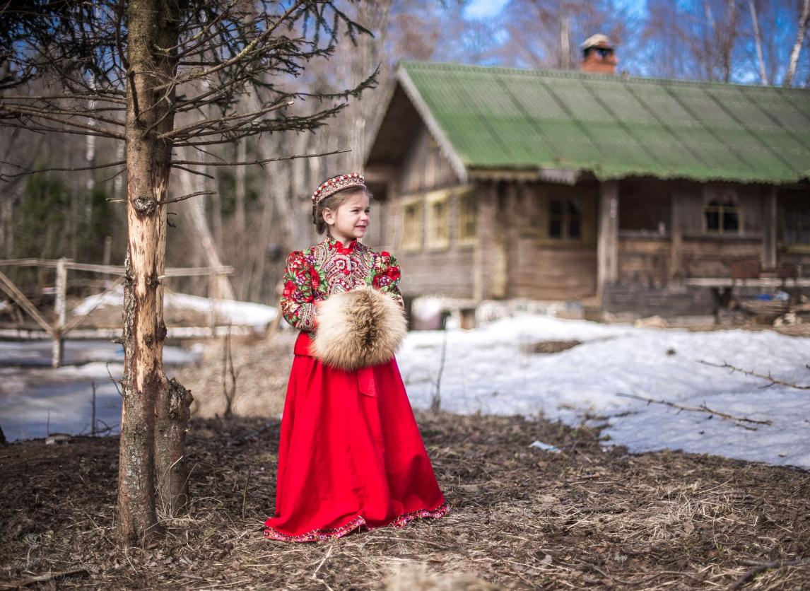 Девочка в платье в русском стиле на фоне деревенского дома