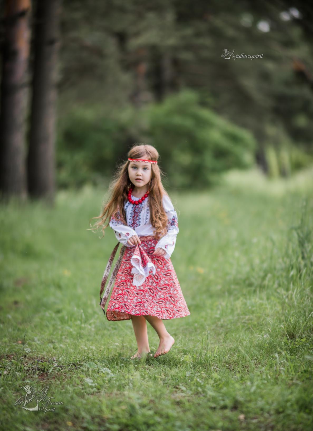 Девочка в русском народном костюме на фоне леса
