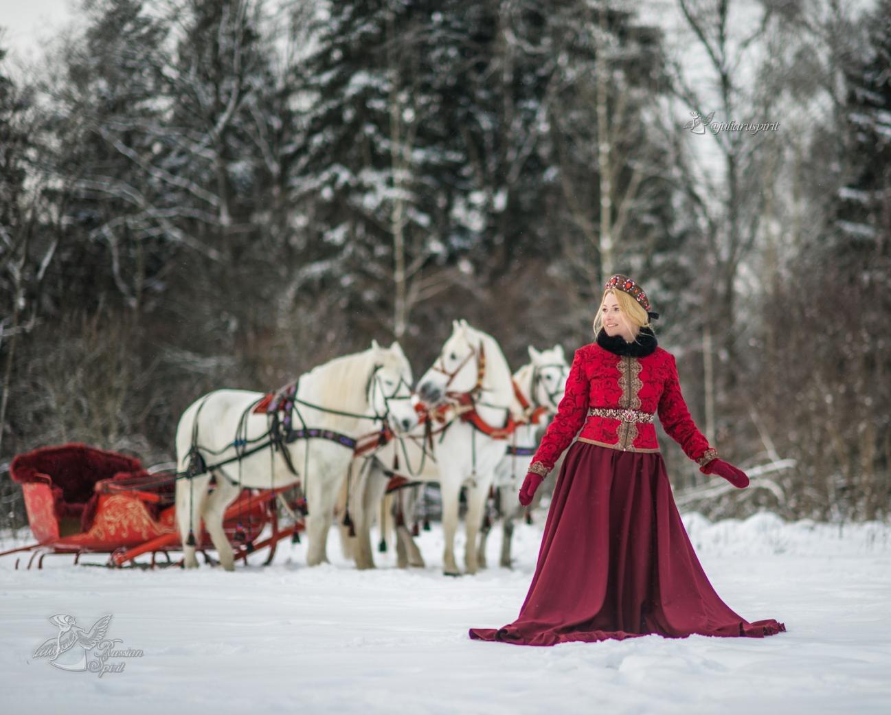 Девушка в русском народном костюме на фоне тройки лошадей