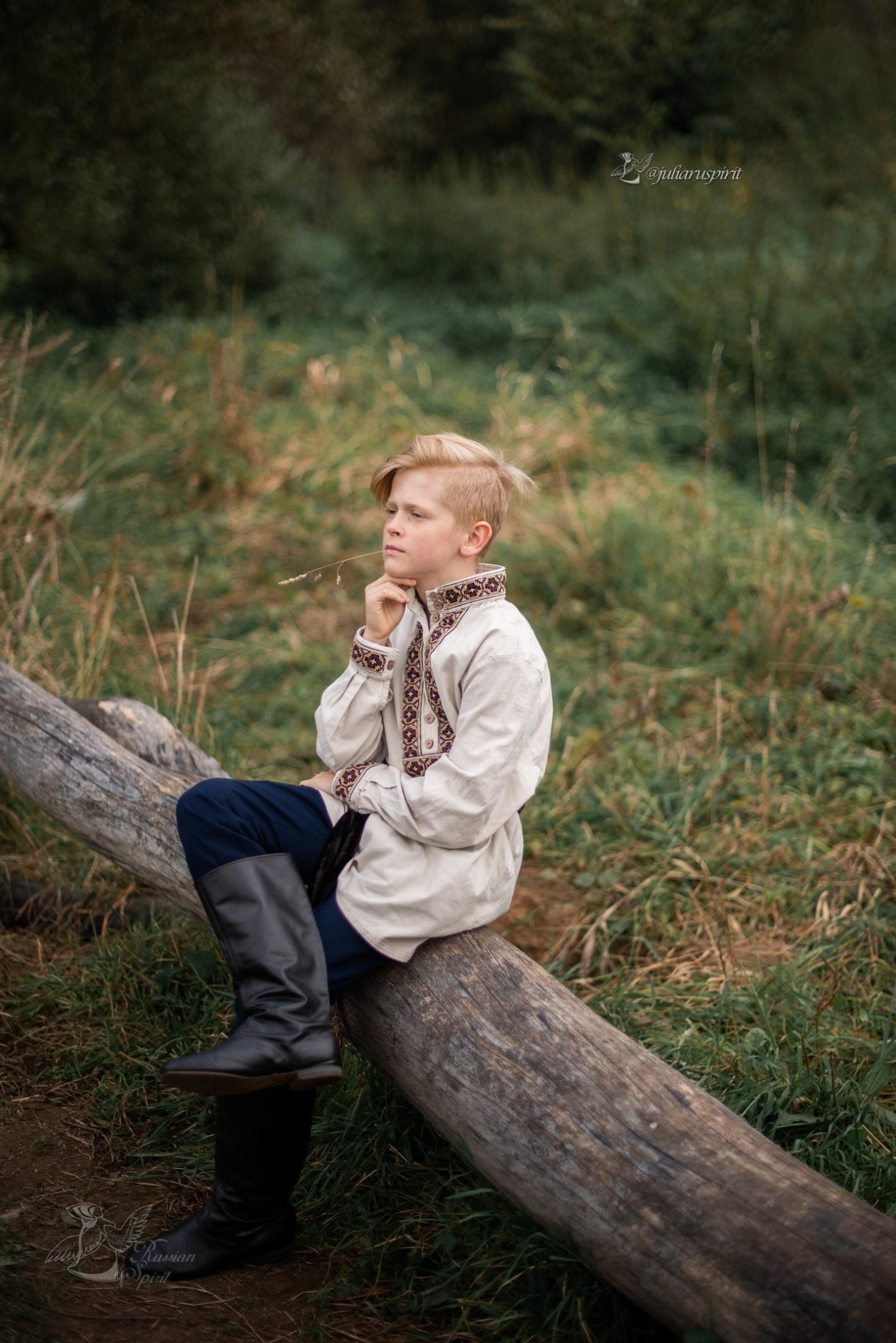 мальчик в льняной рубхе задумался на бревне