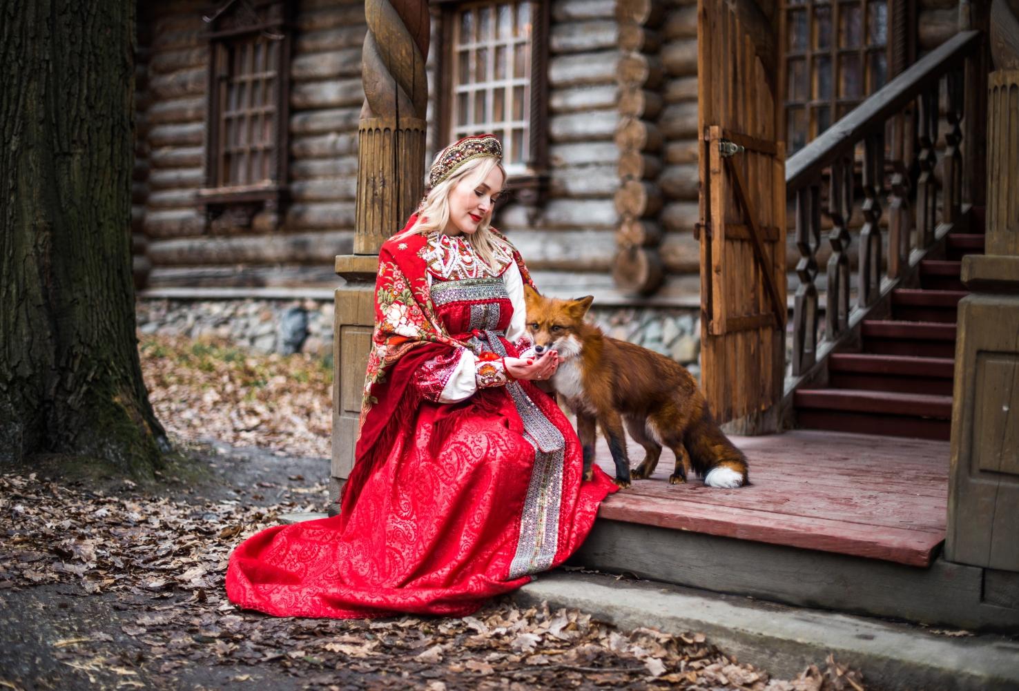девушка в платье в русском стиле с лисой на крылечке у терема