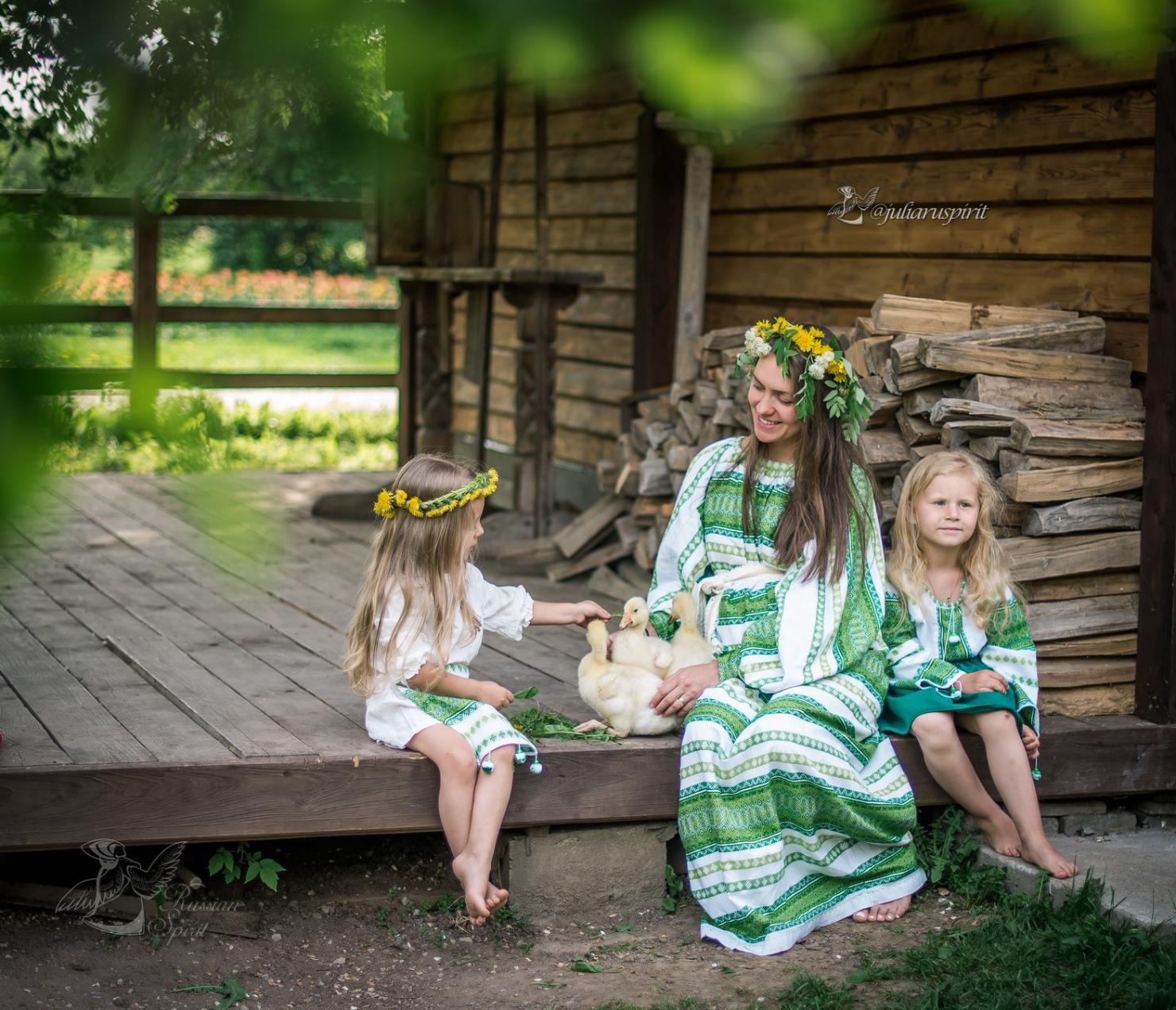 Мама с дочками в русских народных костюмах на крылечке гладят утят
