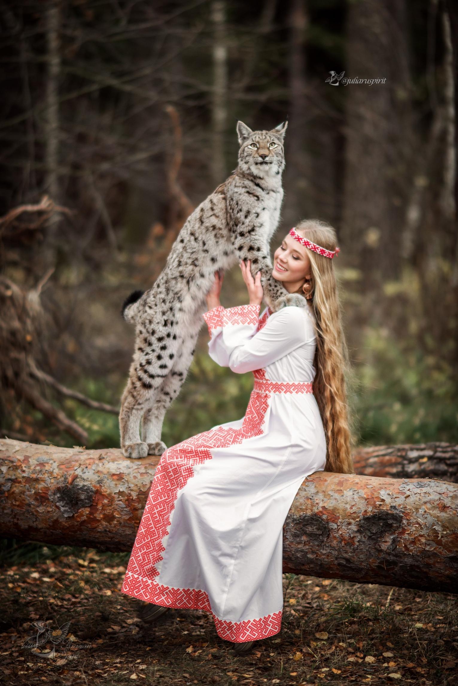 девушка в платье со славянским орнаментом гладит рысь