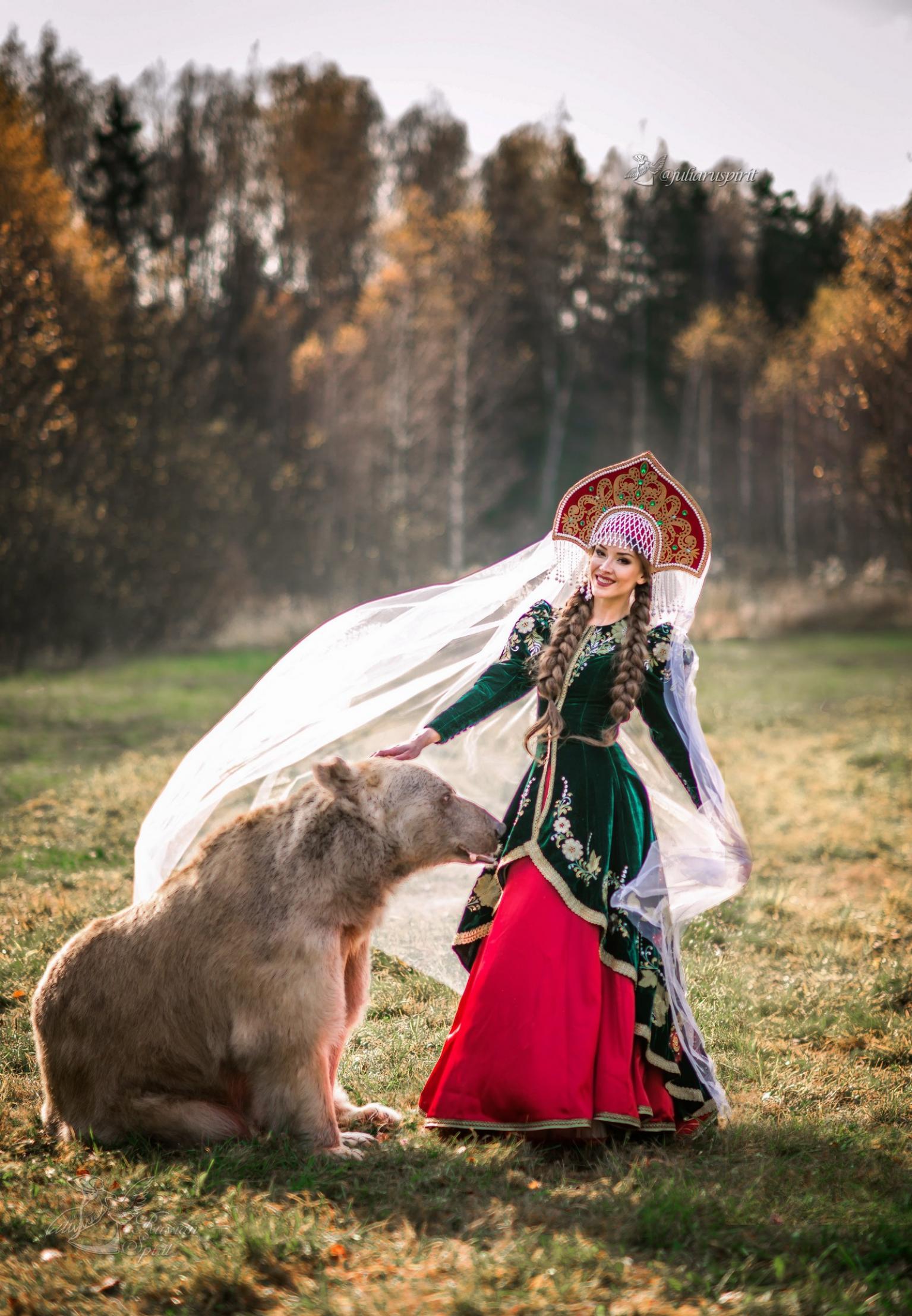 Девушка в вышитом узорами платье в кокошнике с медведем