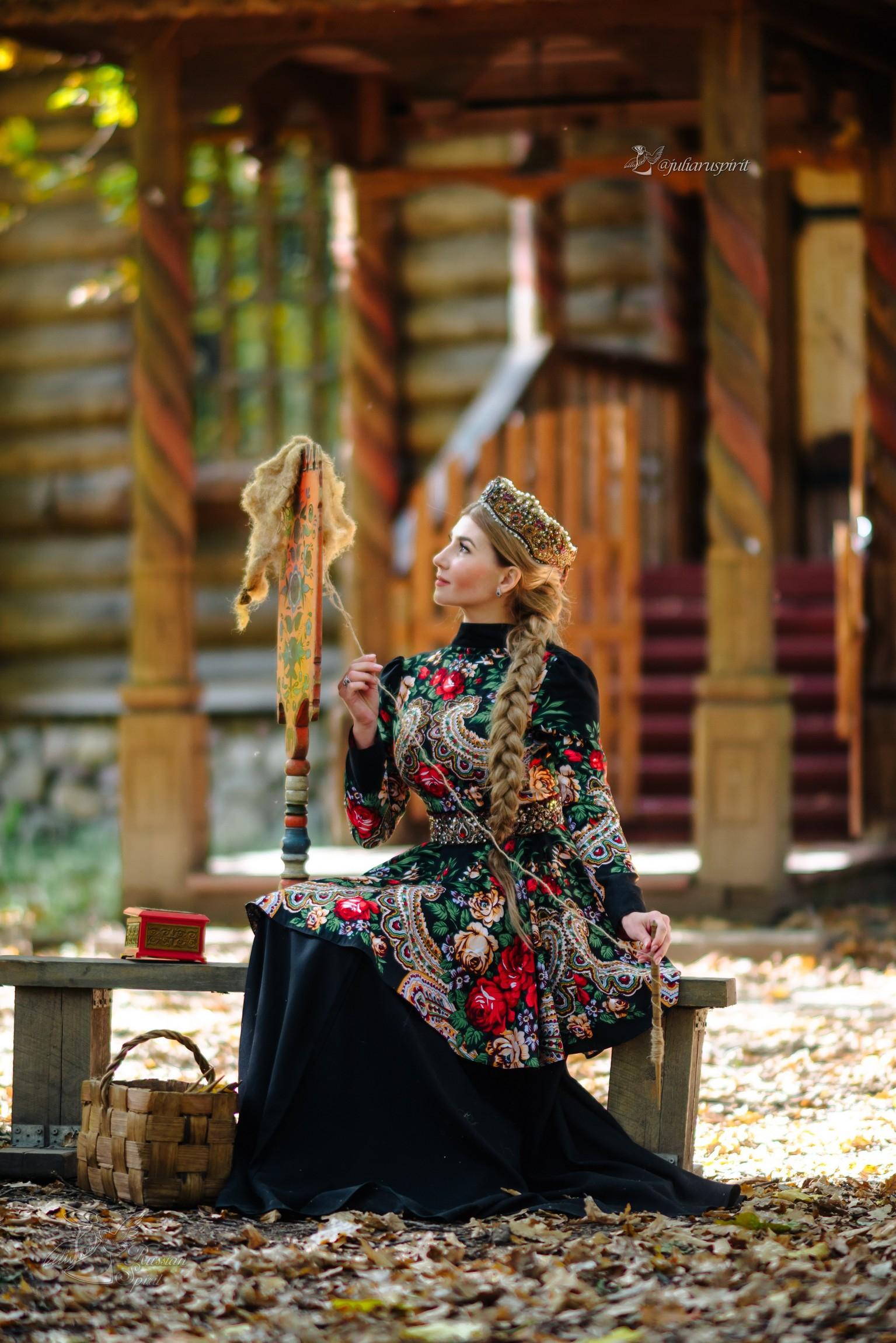 девушка в платье в русском стиле прядёт у терема
