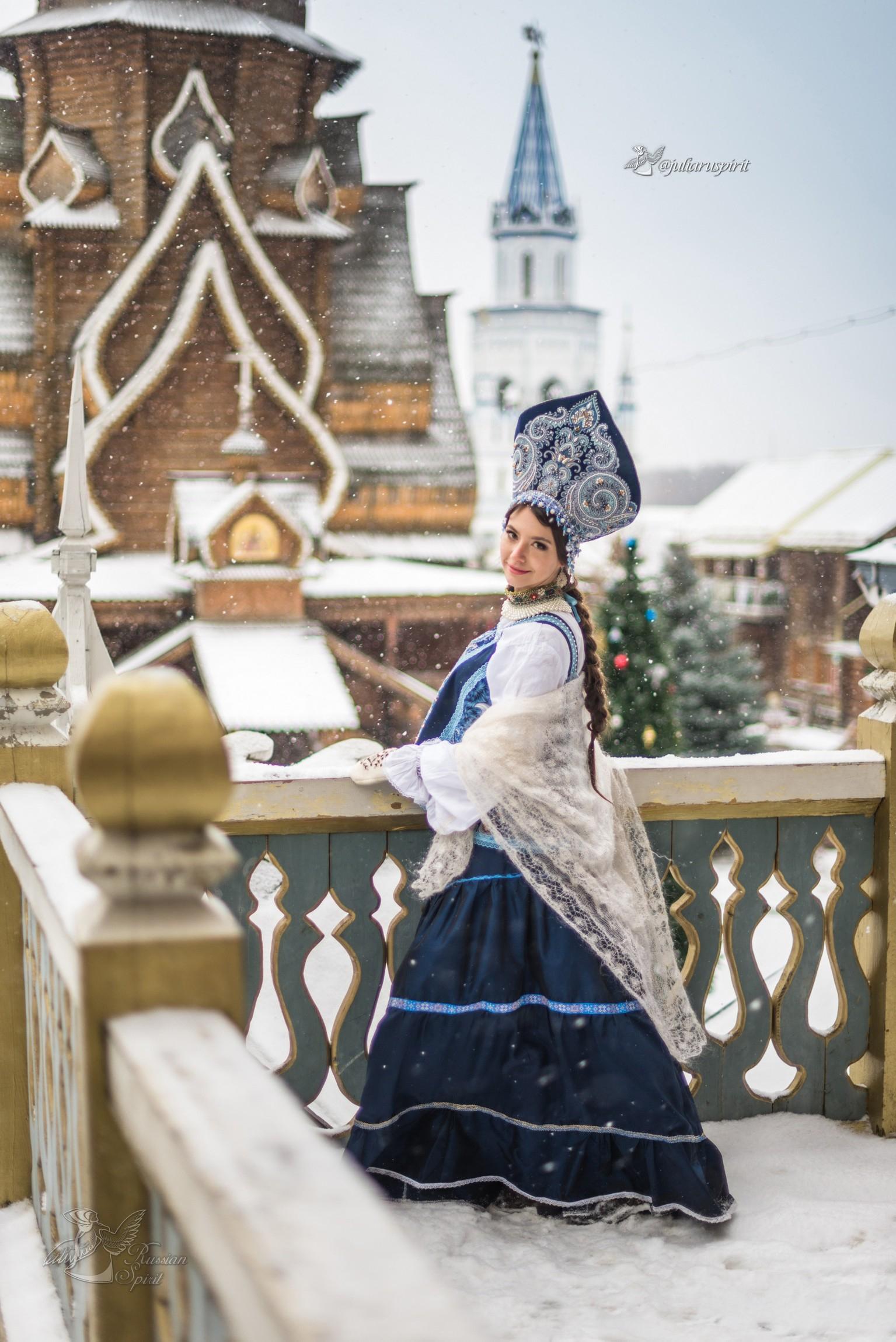 девушка на фоне деревянного кремля в русском стиле зимой