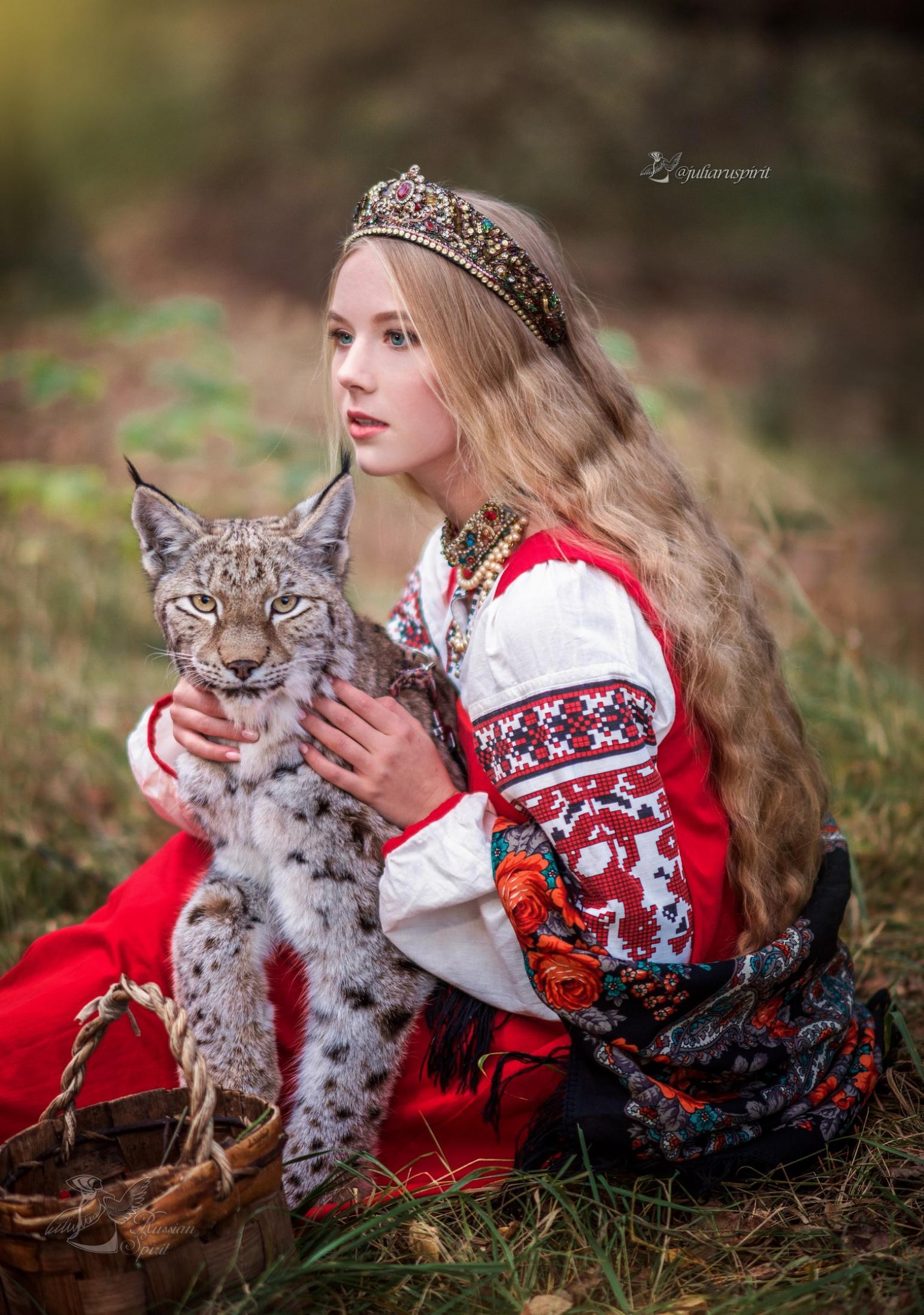 девушка в национальном русском костюме обнимает рысь