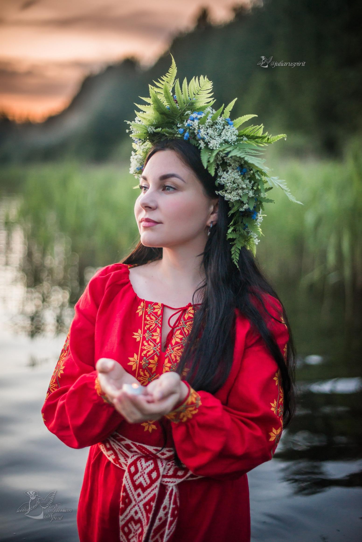 Девушка в красном славянском платье в воде со свечкой на закате Купало