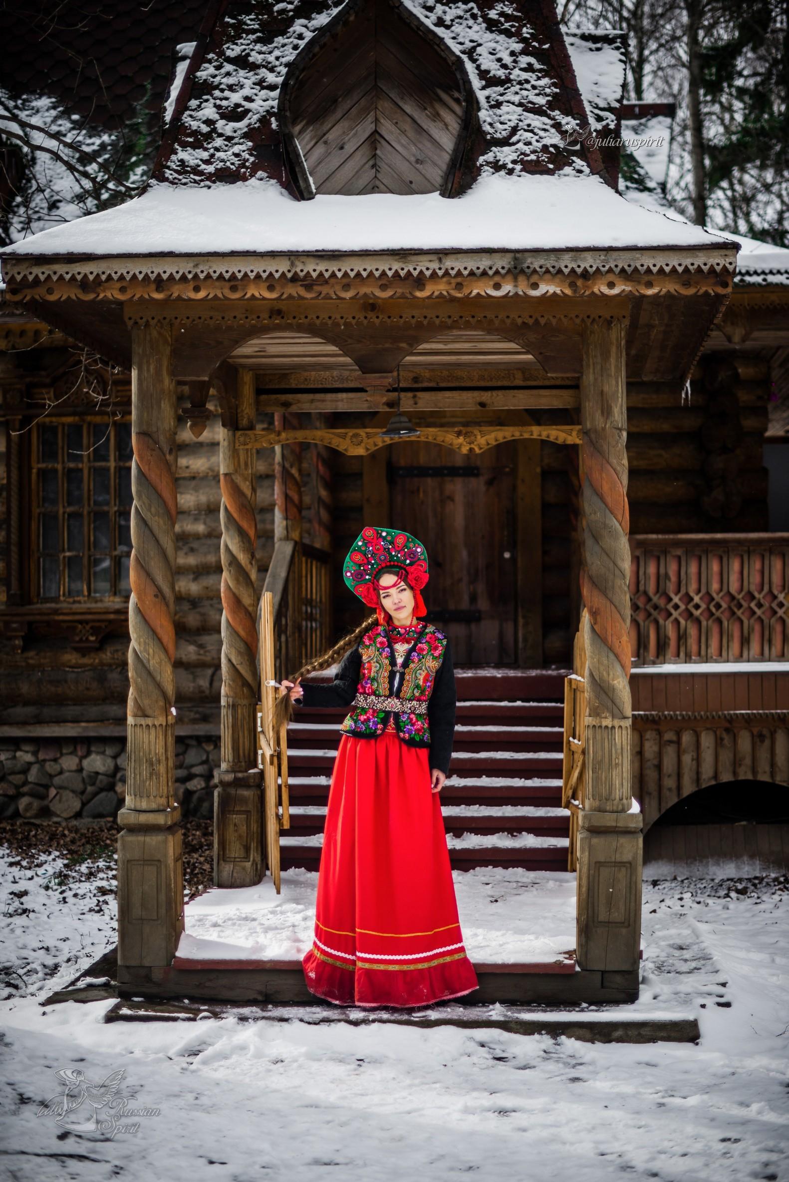 Девушка в жакете на фоне деревянного терема