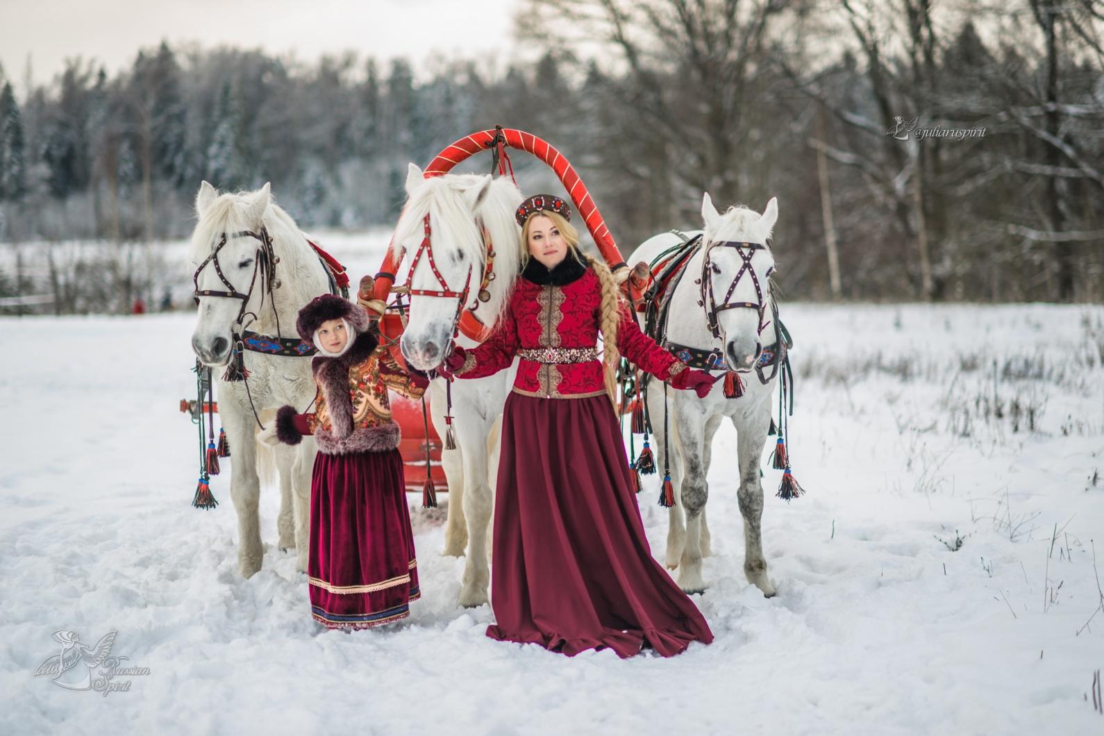 Мама с дочкой в русских народных костюмах с тройкой лошадей