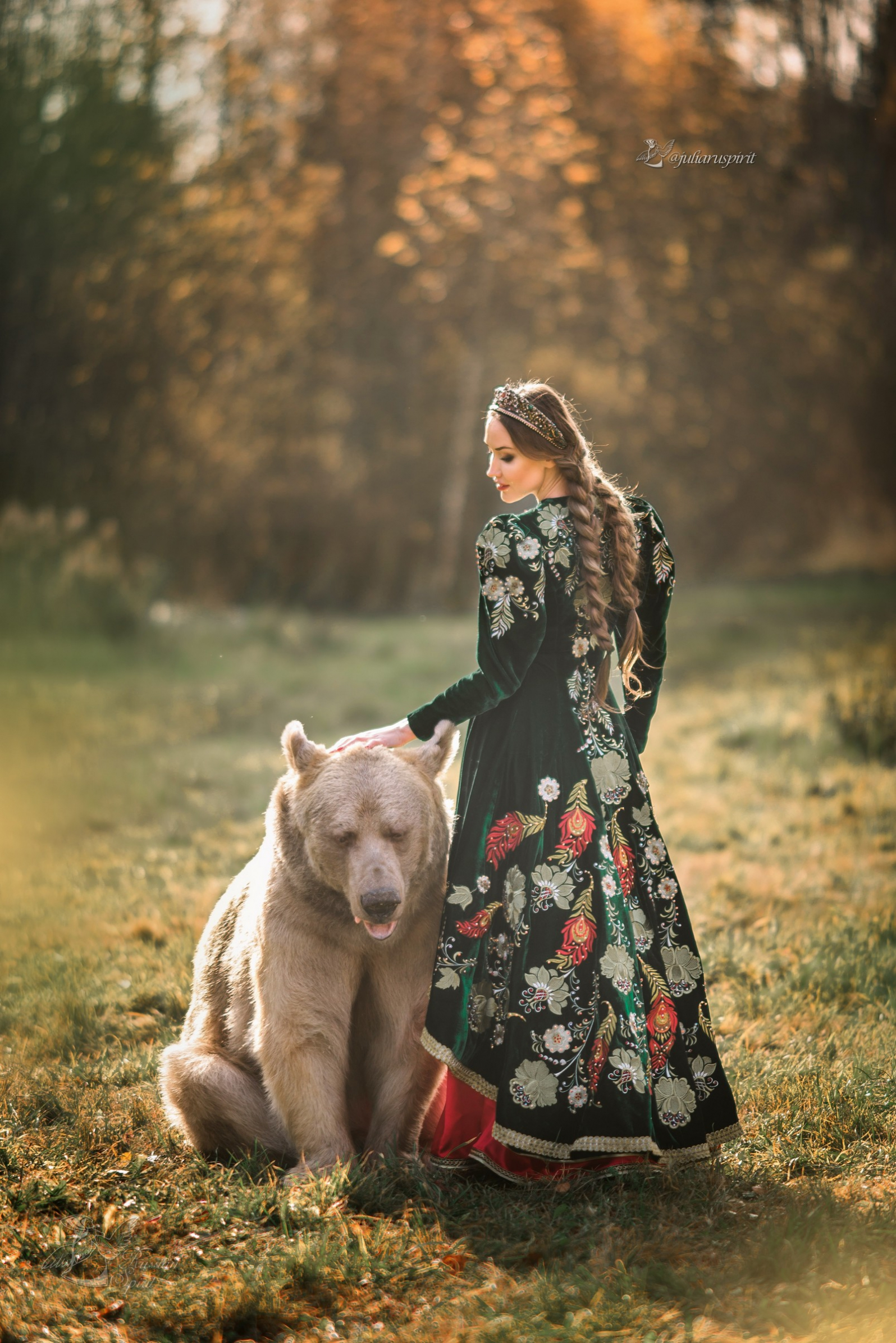 Девушка в вышитом узорами платье гладит медведя