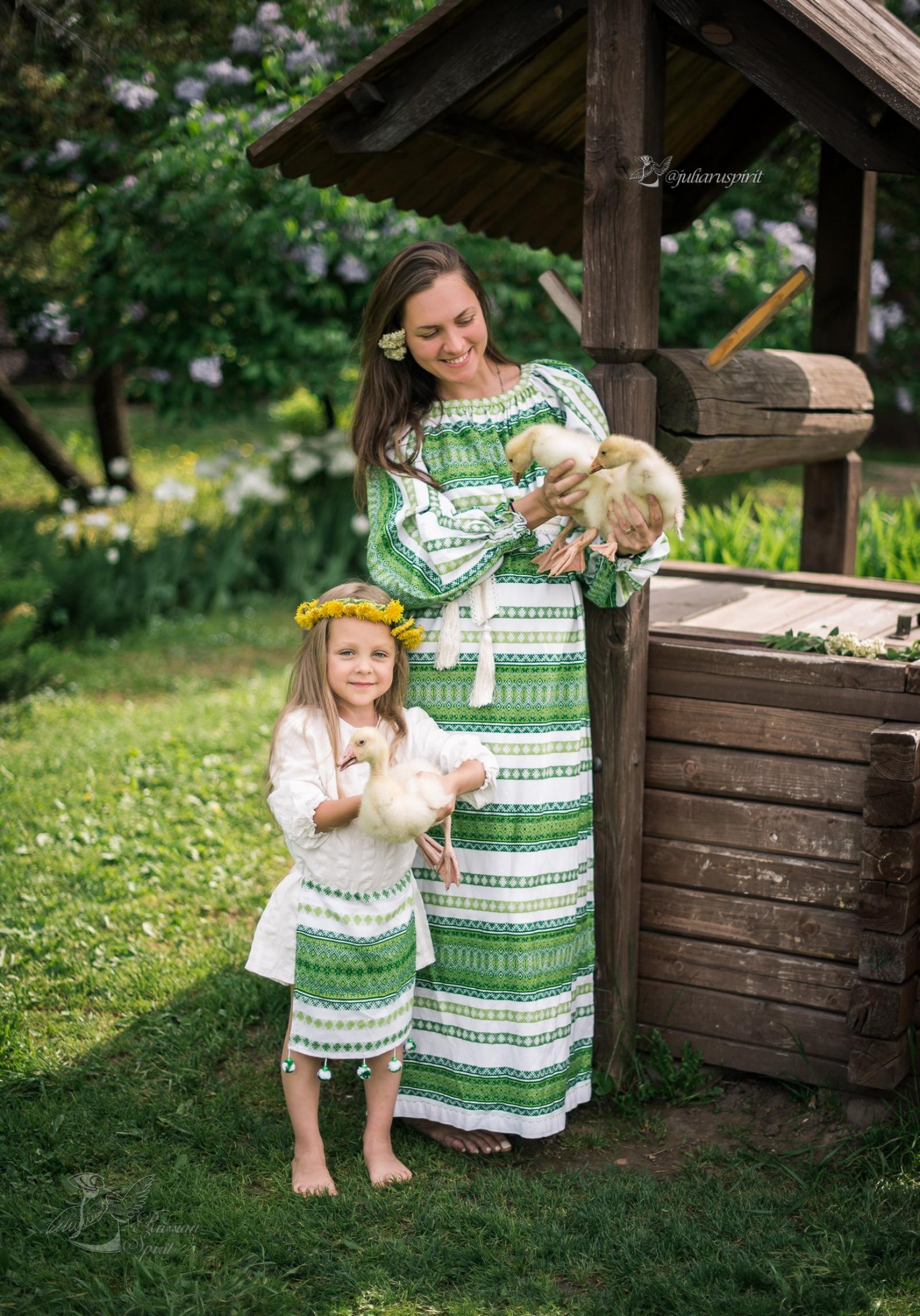 Мама с дочкой в поле в национальных костюмах у колодца с утятами