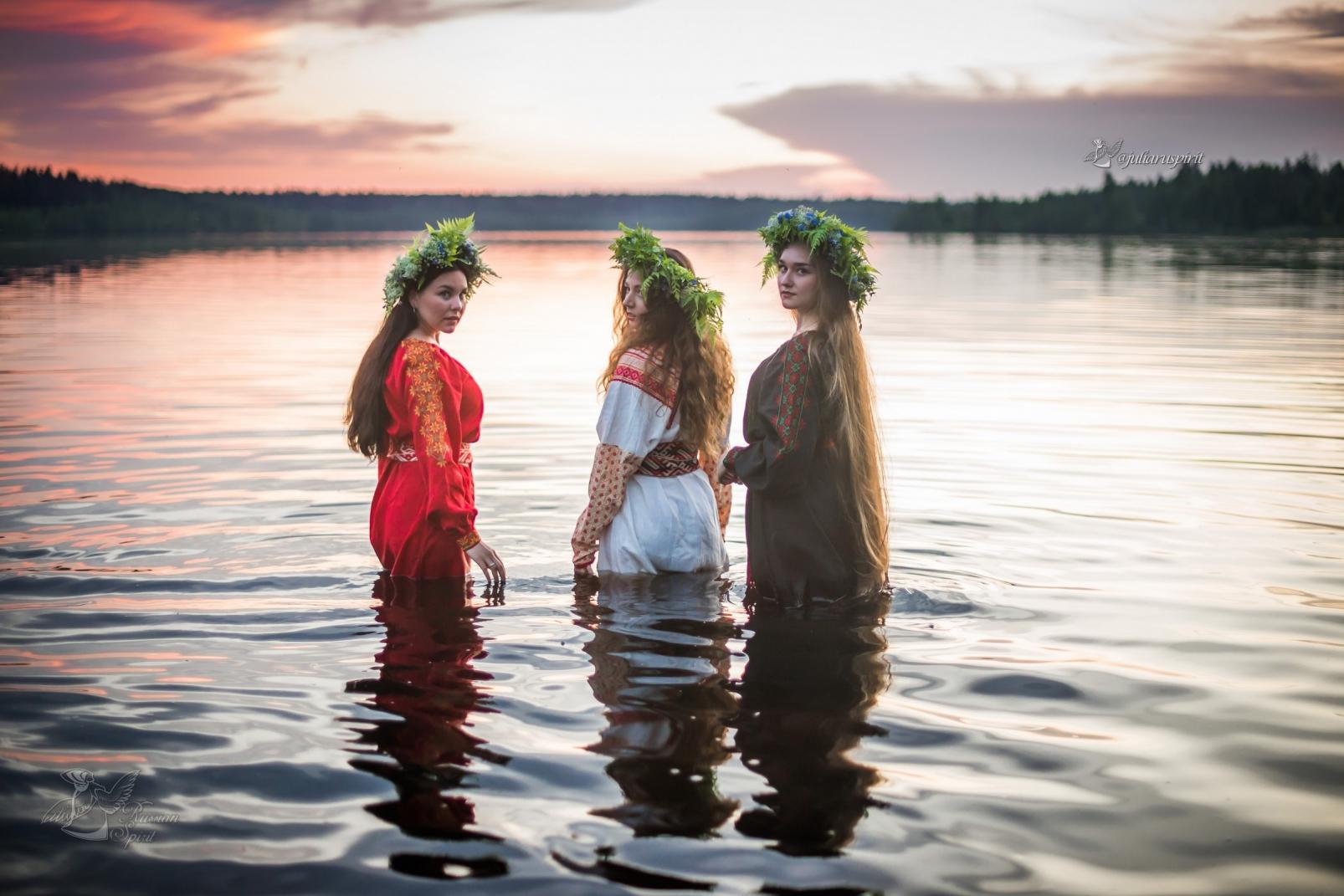 Девушки в славянских платьях в воде на закате Купало