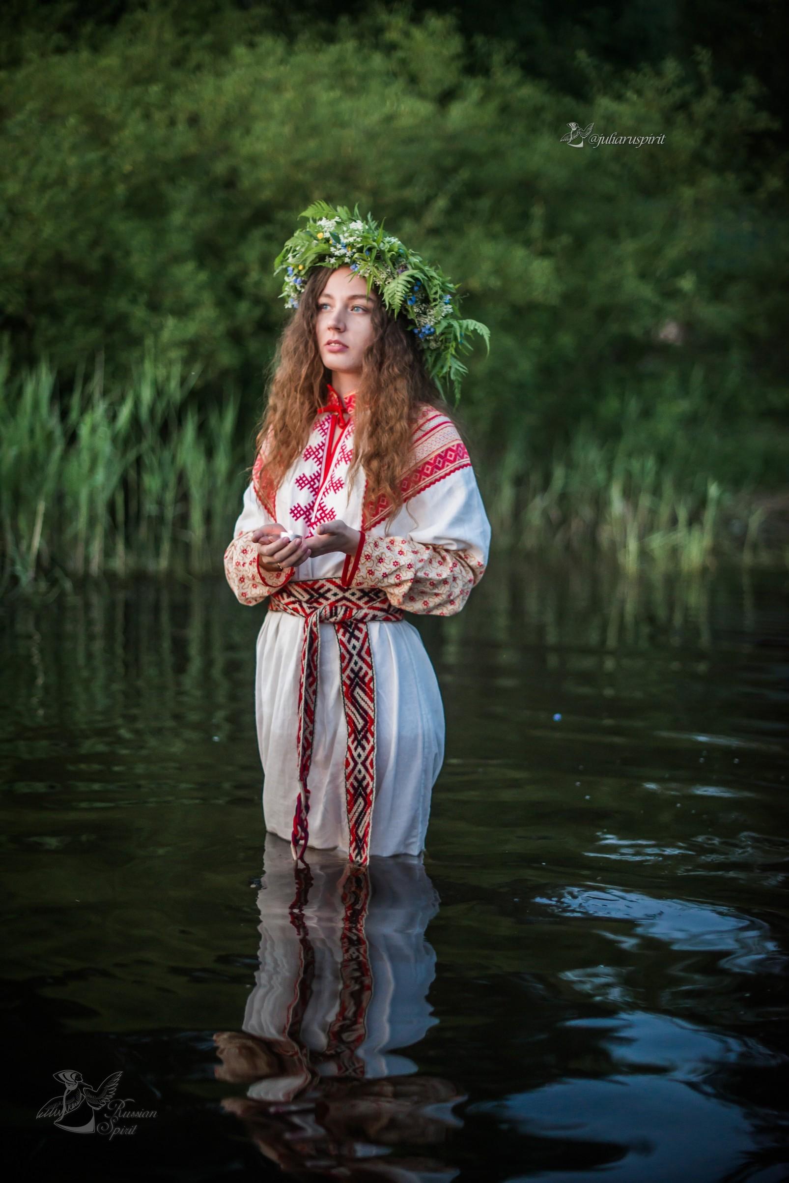 Девушка в славянском платье в воде со свечкой на Купало