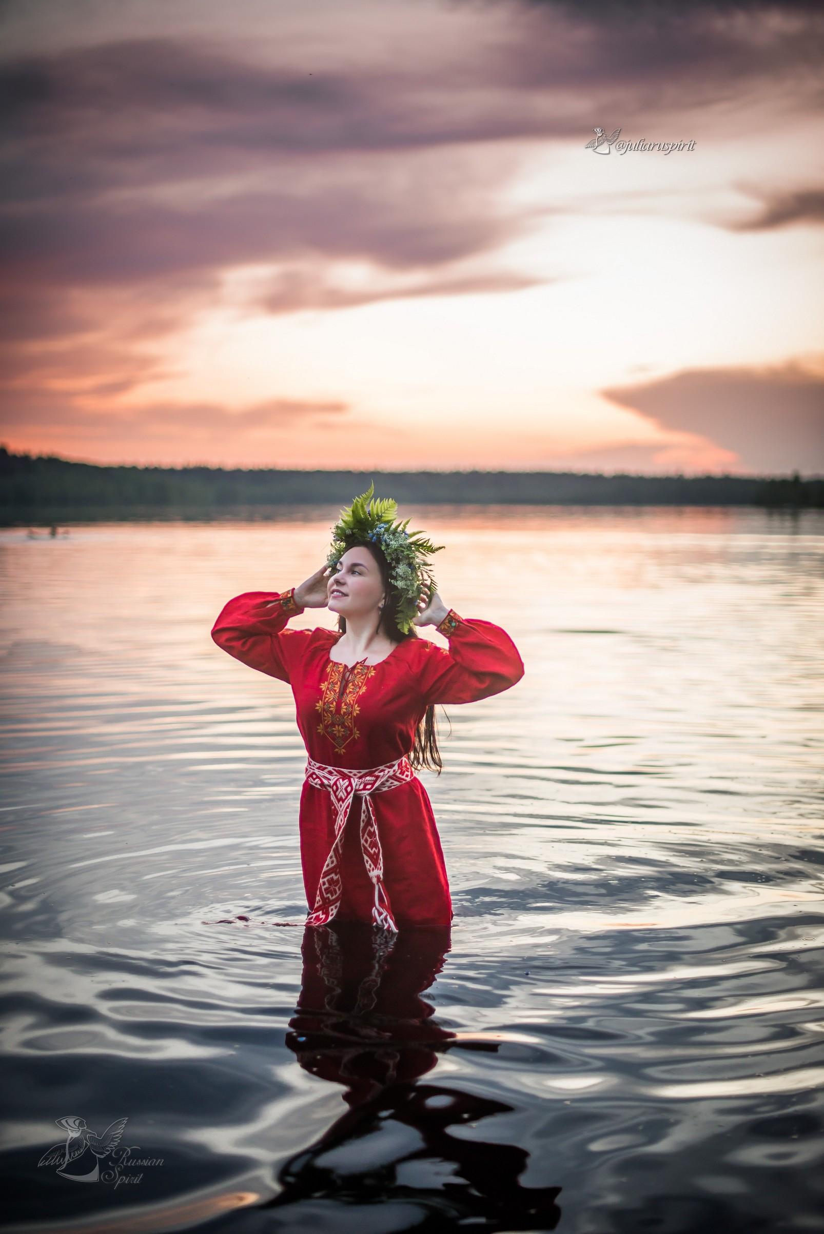 Девушка в красном славянском платье в воде на закате Купало