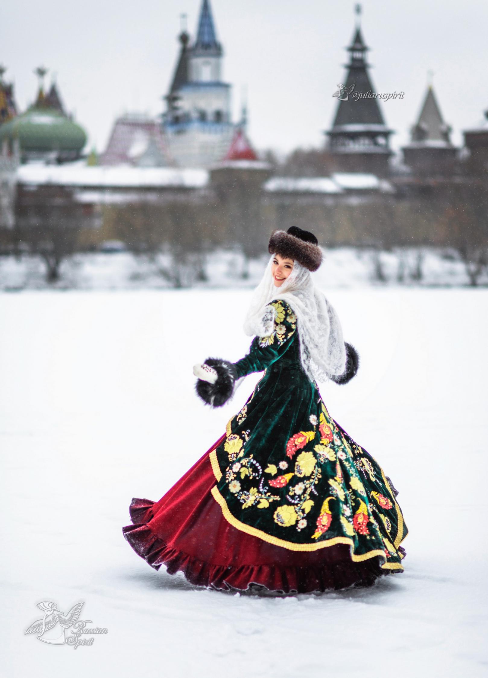 Девушка в вышитом узорами платье на фотосессии кружится на фоне кремля