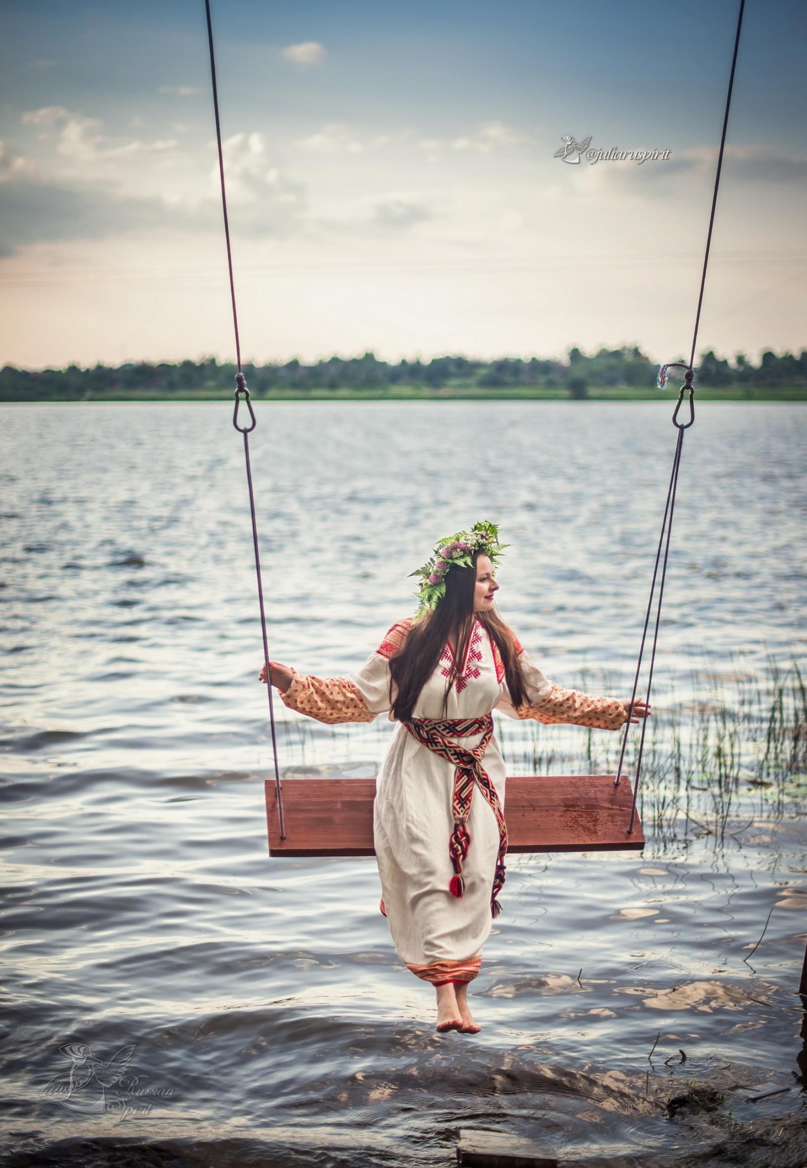 Девушка в славянском платье на качелях на фоне воды