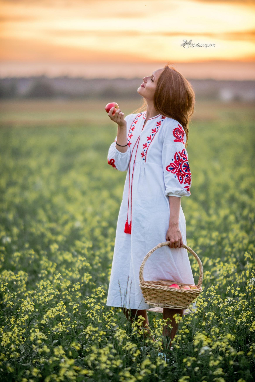 Девушка с корзинкой яблок в цветущем поле