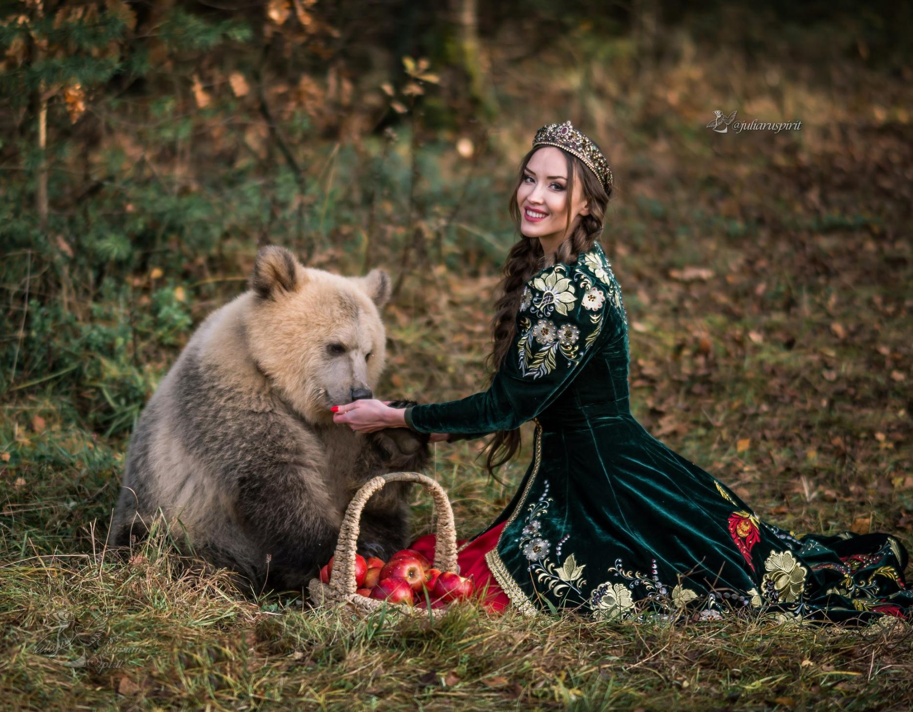 Девушка в вышитом узорами платье в кокошнике кормит медвежонка