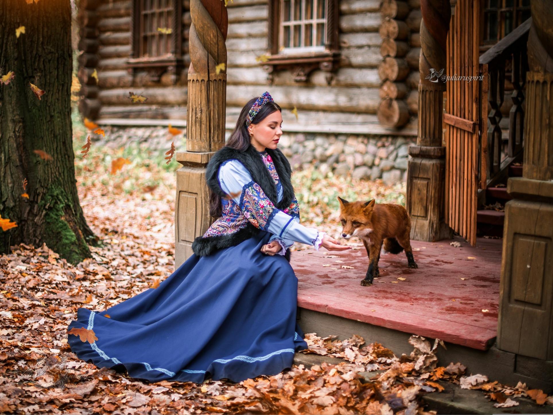Девушка в костюме в русском стиле кормит лису на крылечке