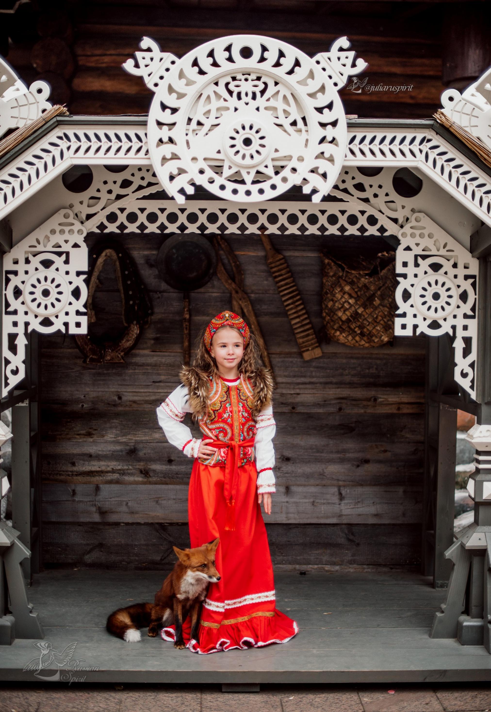 Девочка в платье в русском стиле на фоне стены дома с вырезными узорами