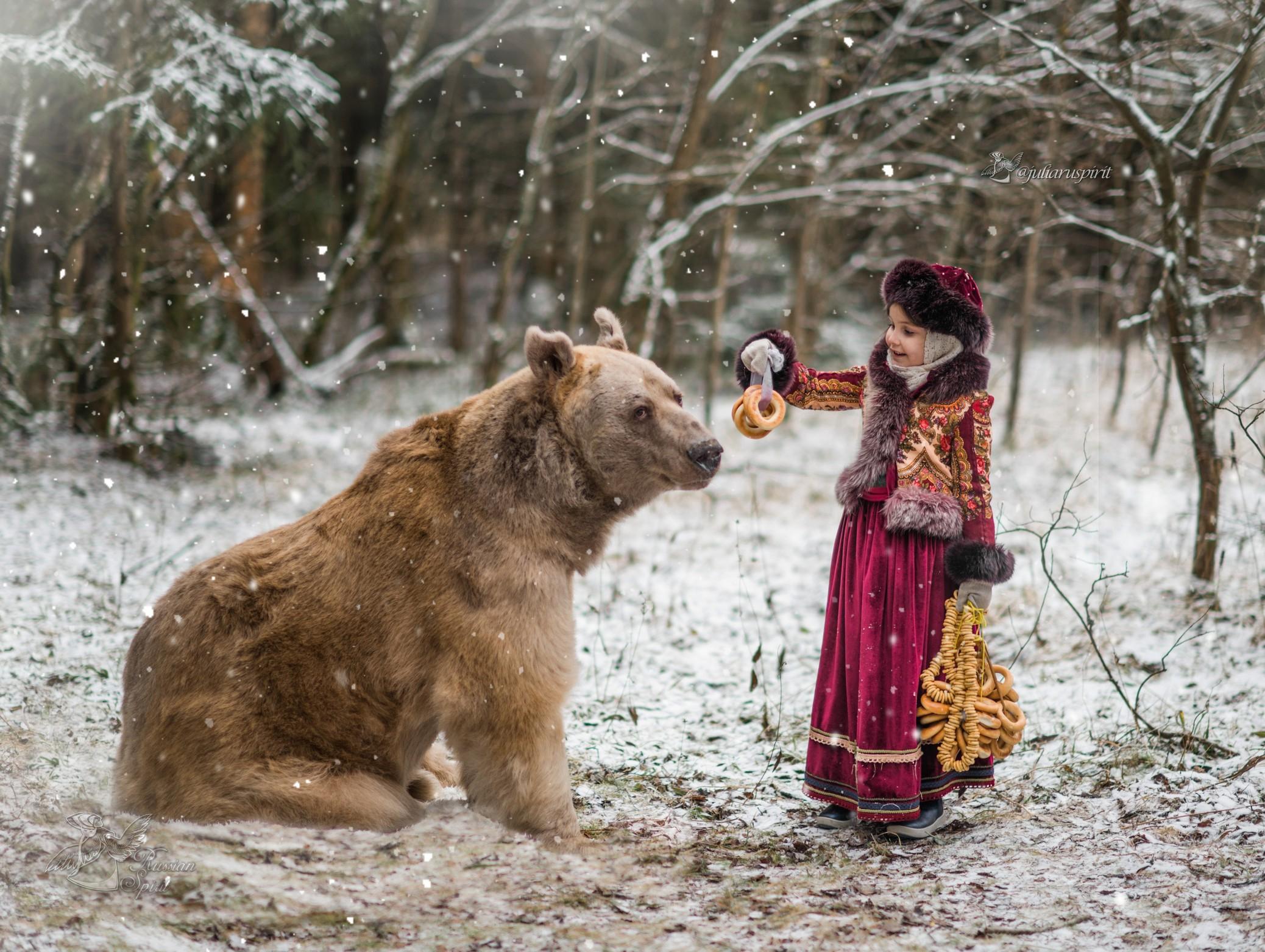 Девочка кормит медведя баранками