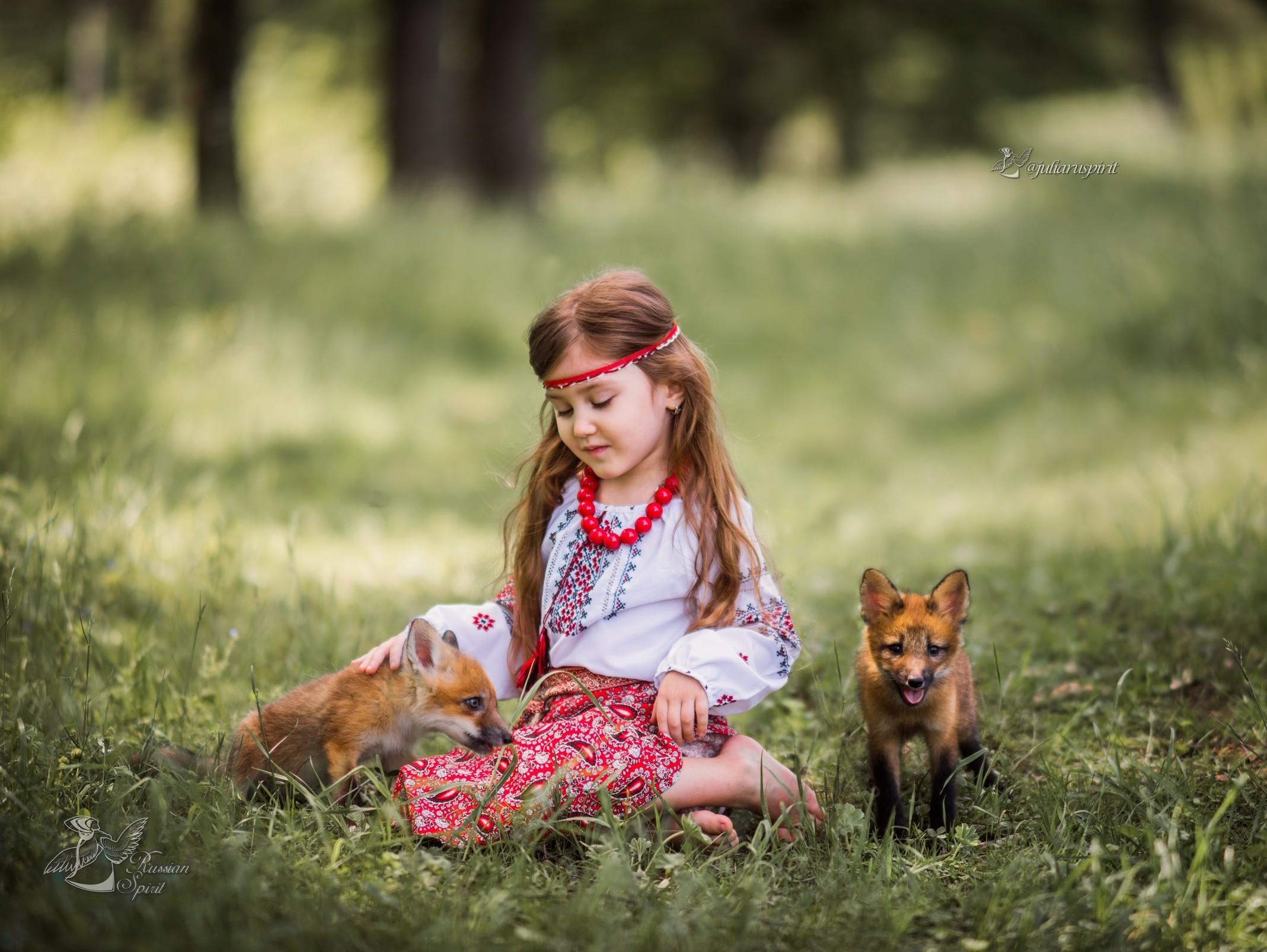 Девочка в русском народном костюме с лисятами на лужайке сидит