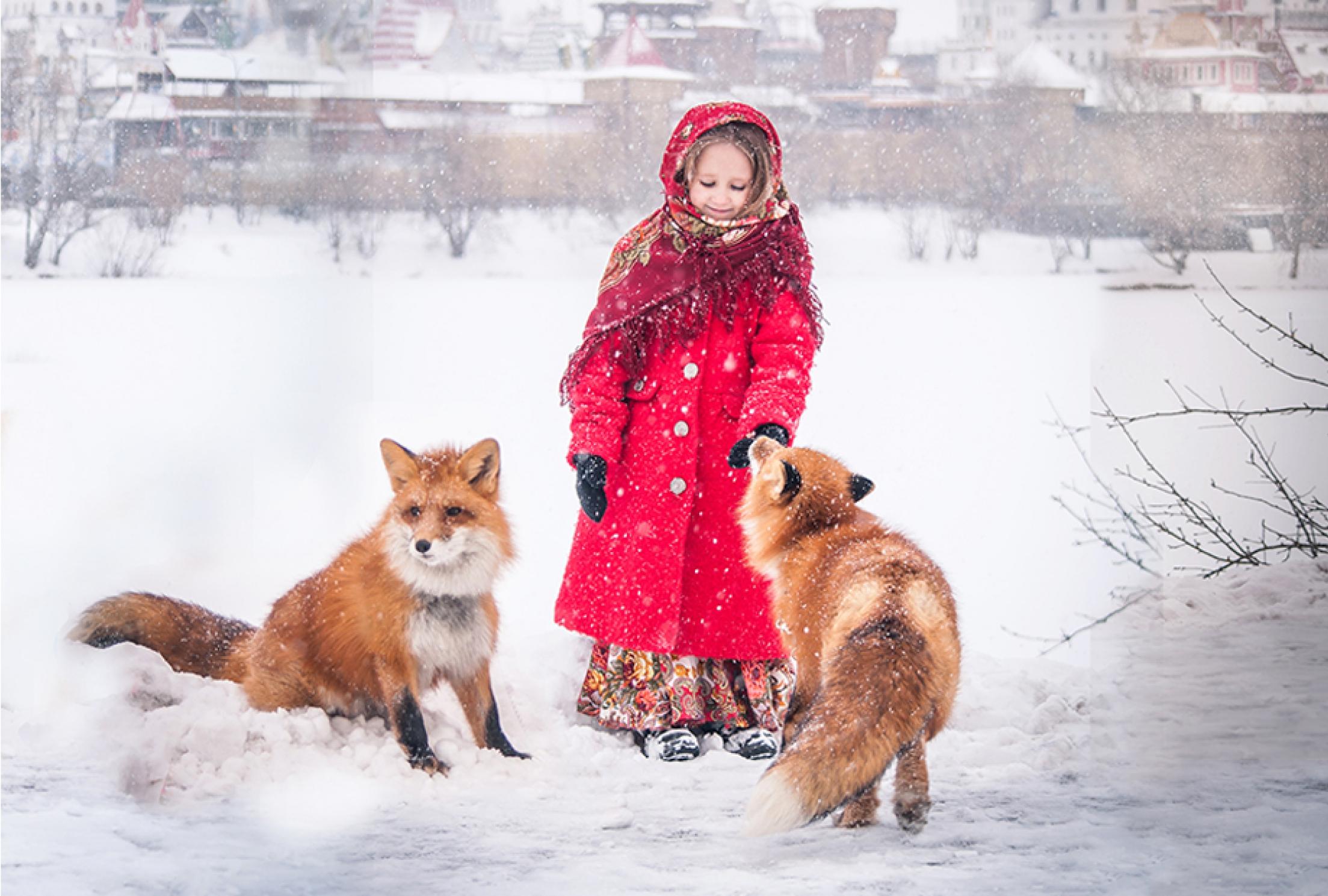 Девочка в красном пальто с лисами на фоне кремля