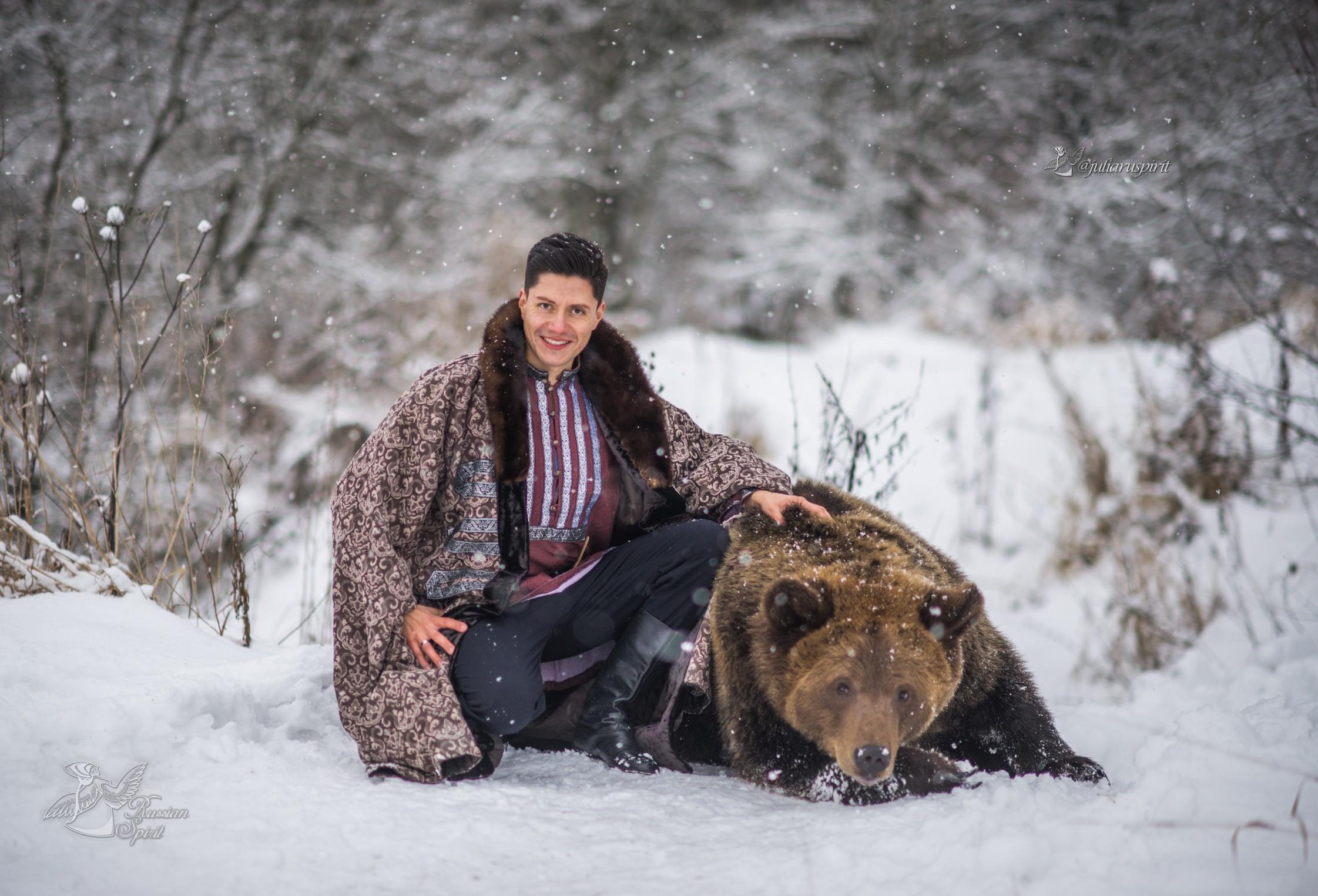 Мужчина в боярской шубе с медведем на фотосессии