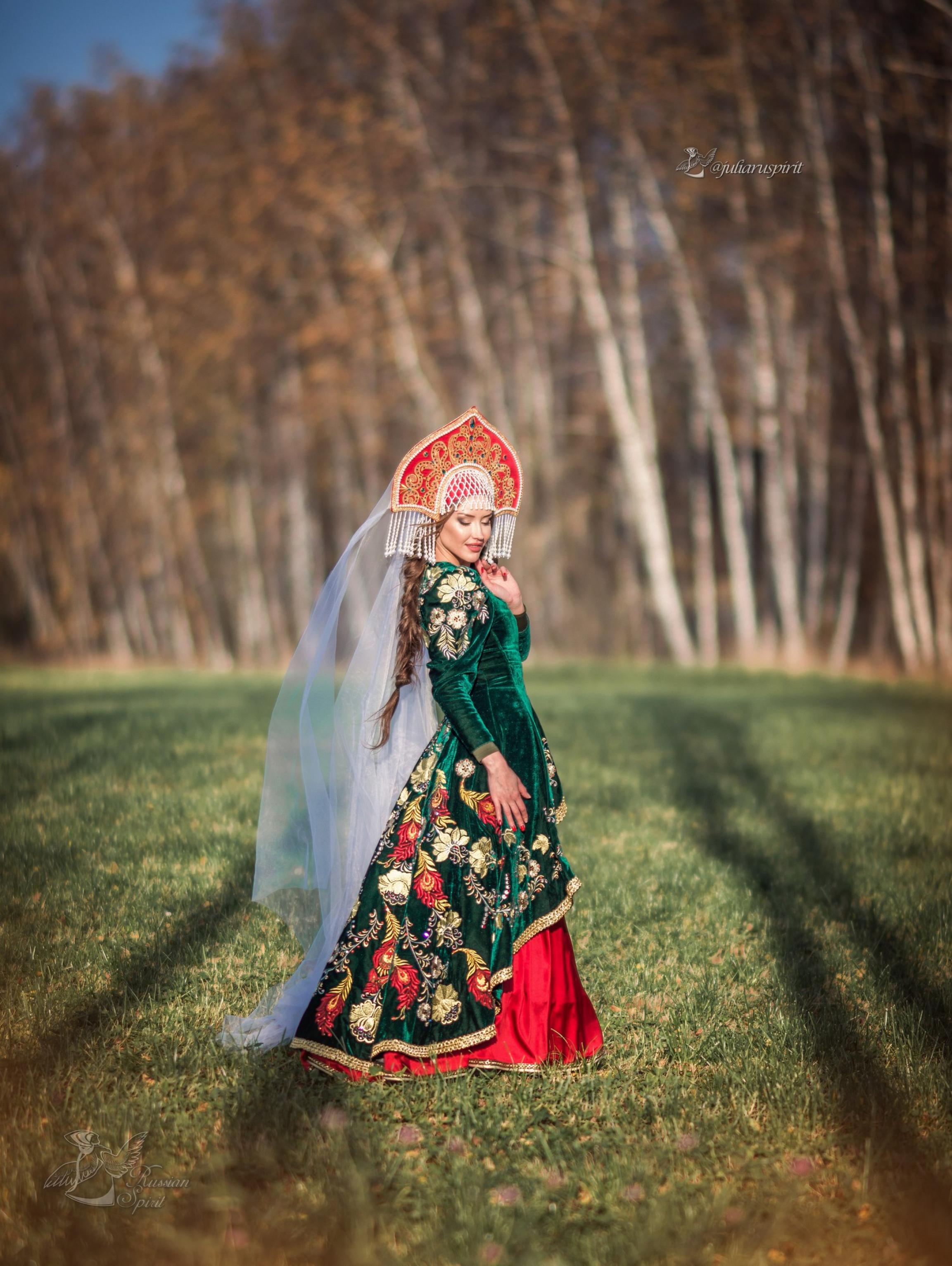 Девушка в вышитом узорами платье в кокошнике на фоне леса