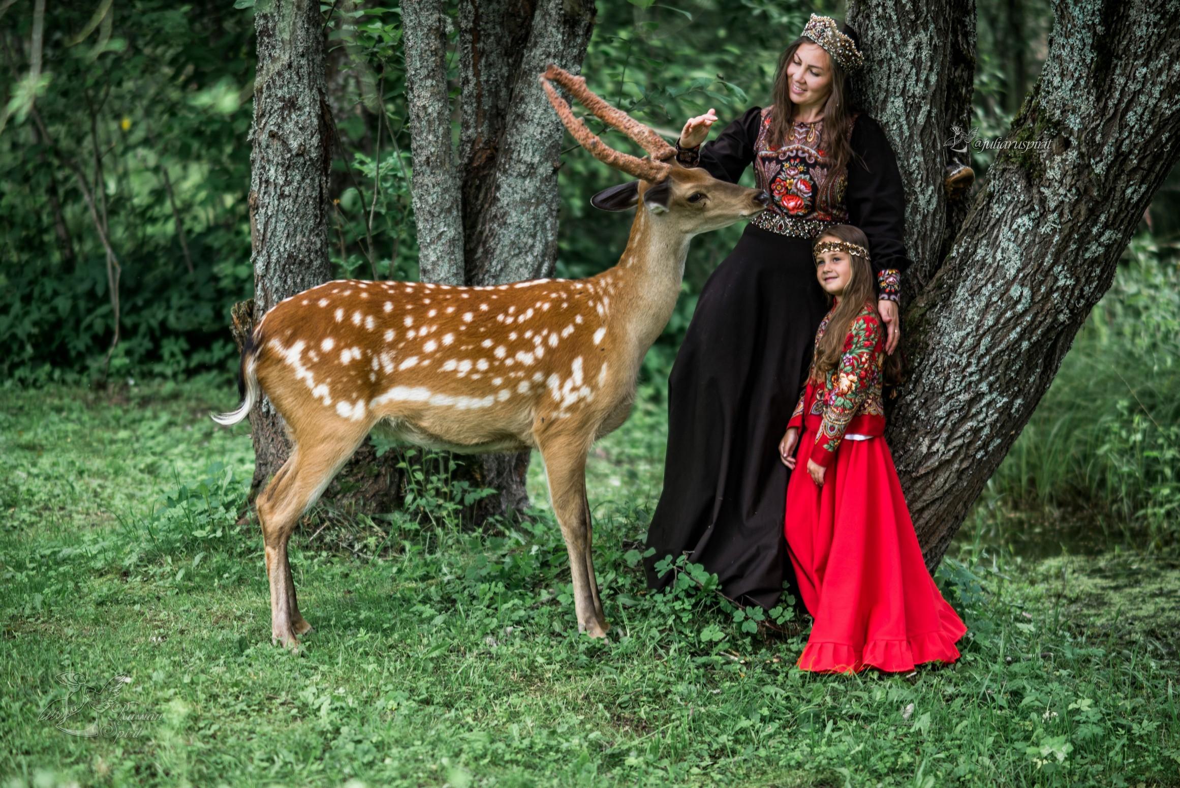 Мама с дочкой в костюмах в русском стиле гладят оленя