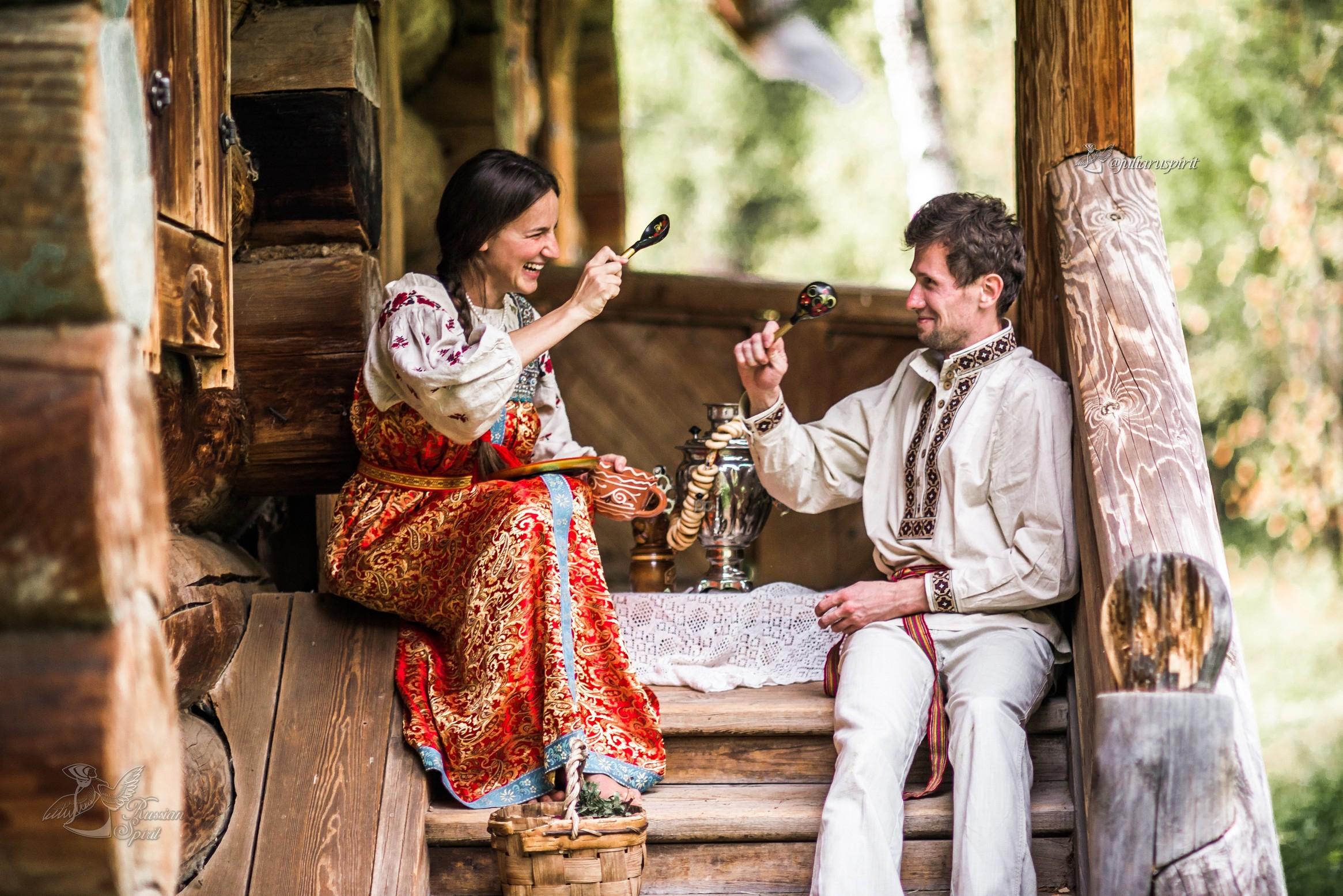Девушка и парень пьют чай из самовара на крылечке деревянного дома в русском стиле