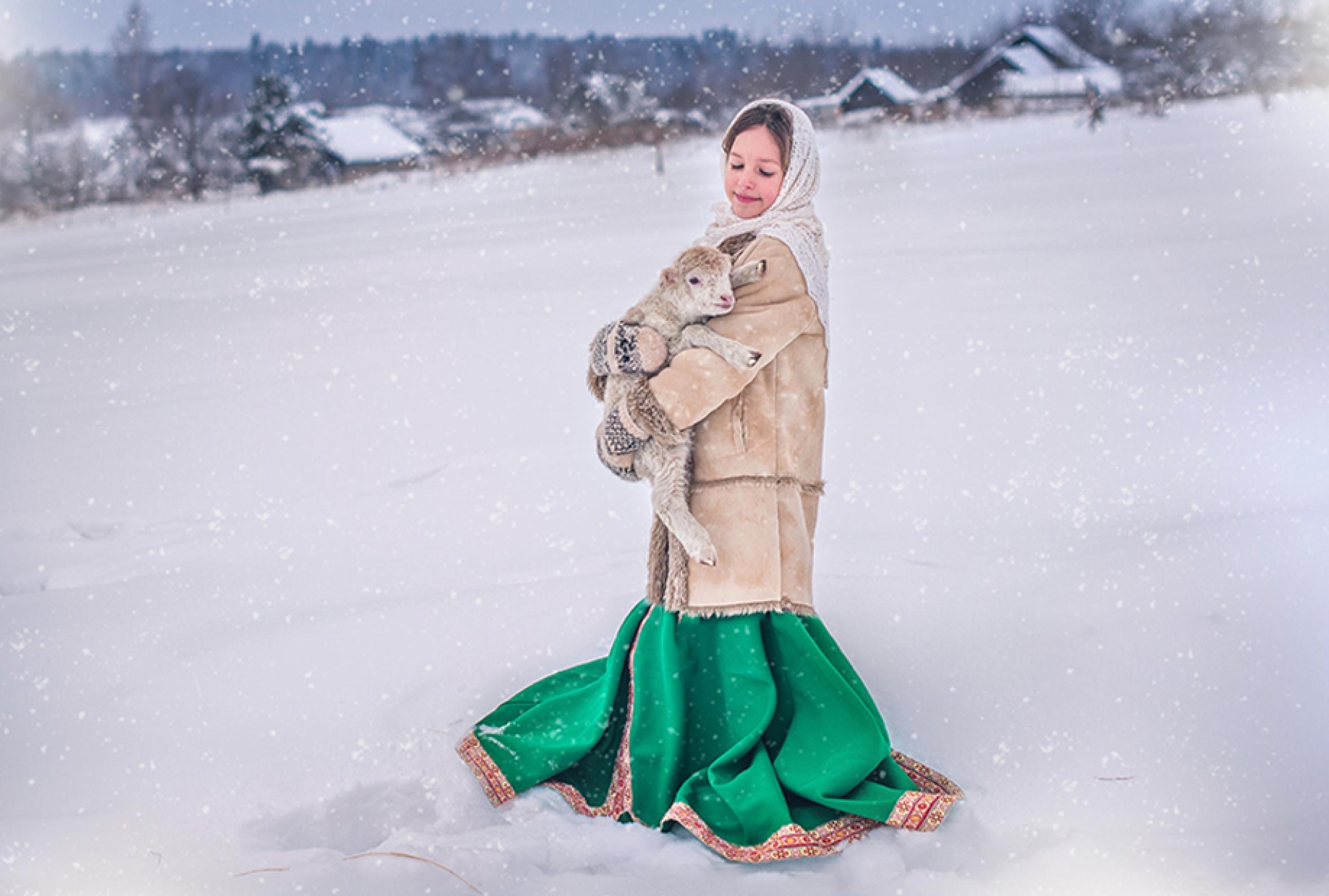 Девочка в тулупчике в поле с ягненком на руках