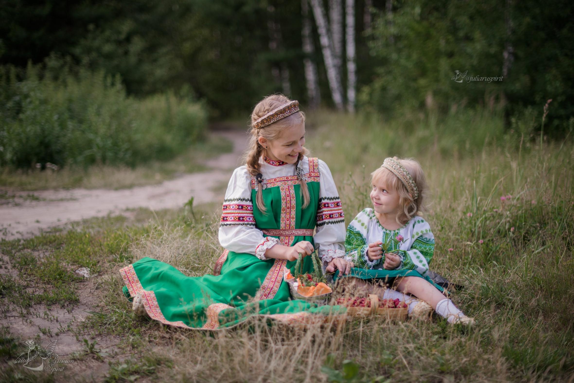 Сестрёнки в русских народных платьях отдыхают на лесной лужайке