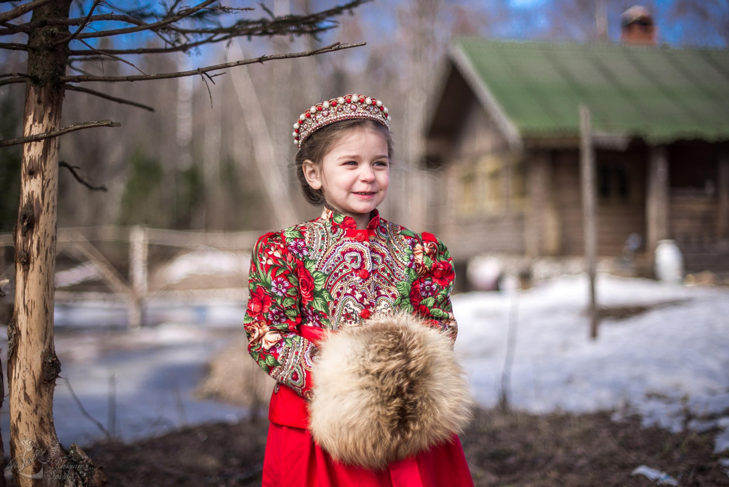Девочка в платье в русском стиле на фоне деревянного дома
