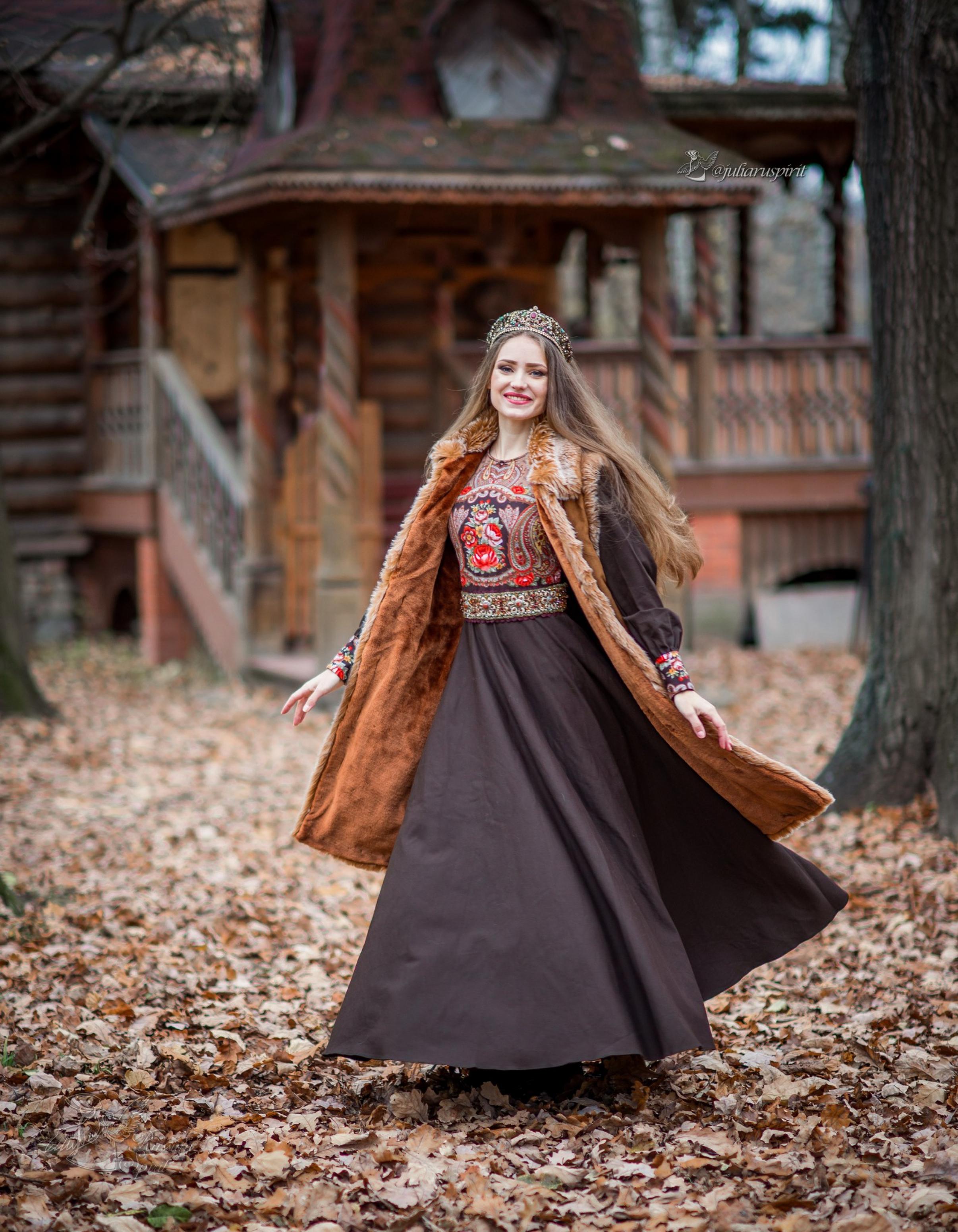 Девушка в коричневом платье в русском стиле и в меховой жилетке на фоне терема
