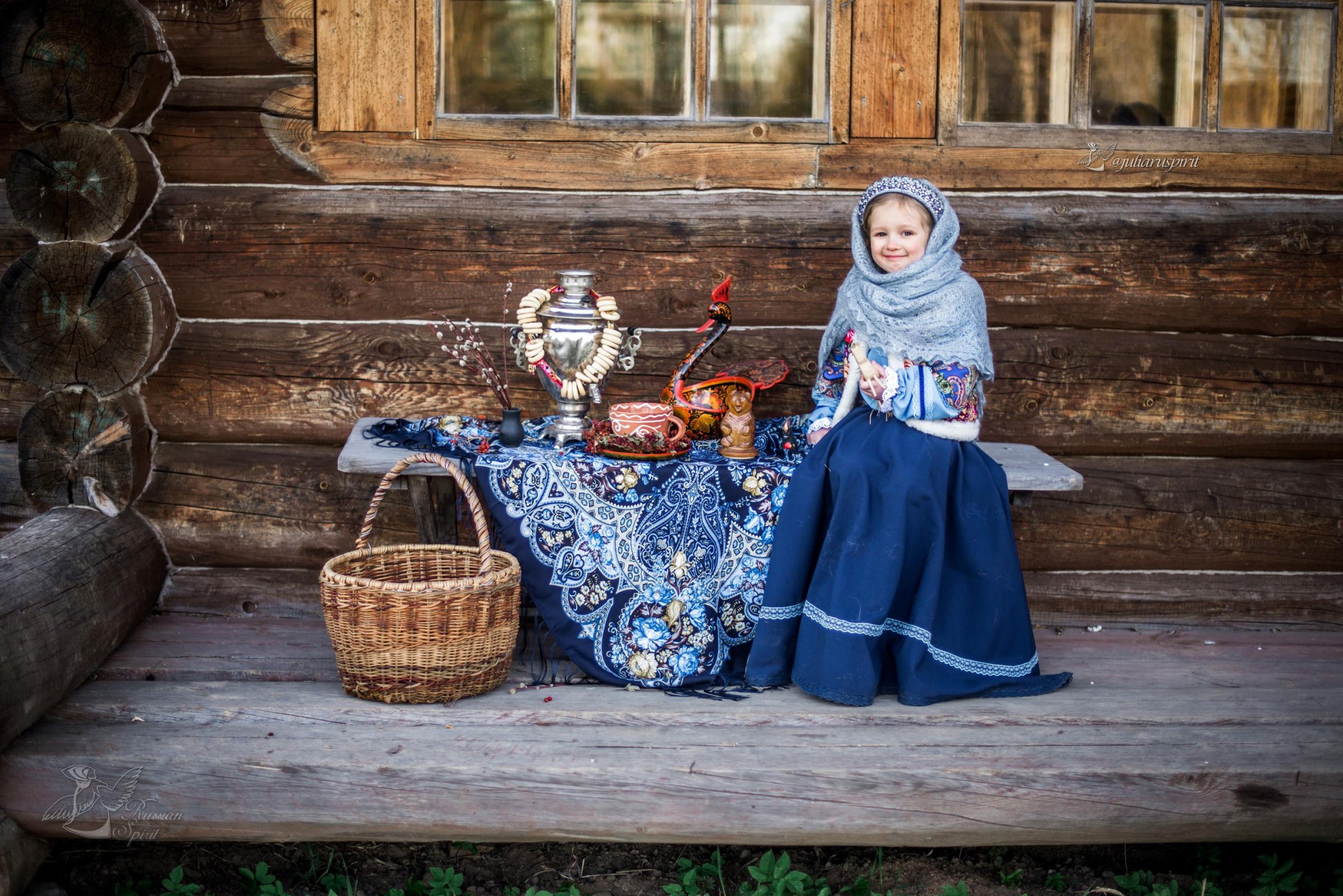 Девочка в национальном русском костюме на лавочке у дома