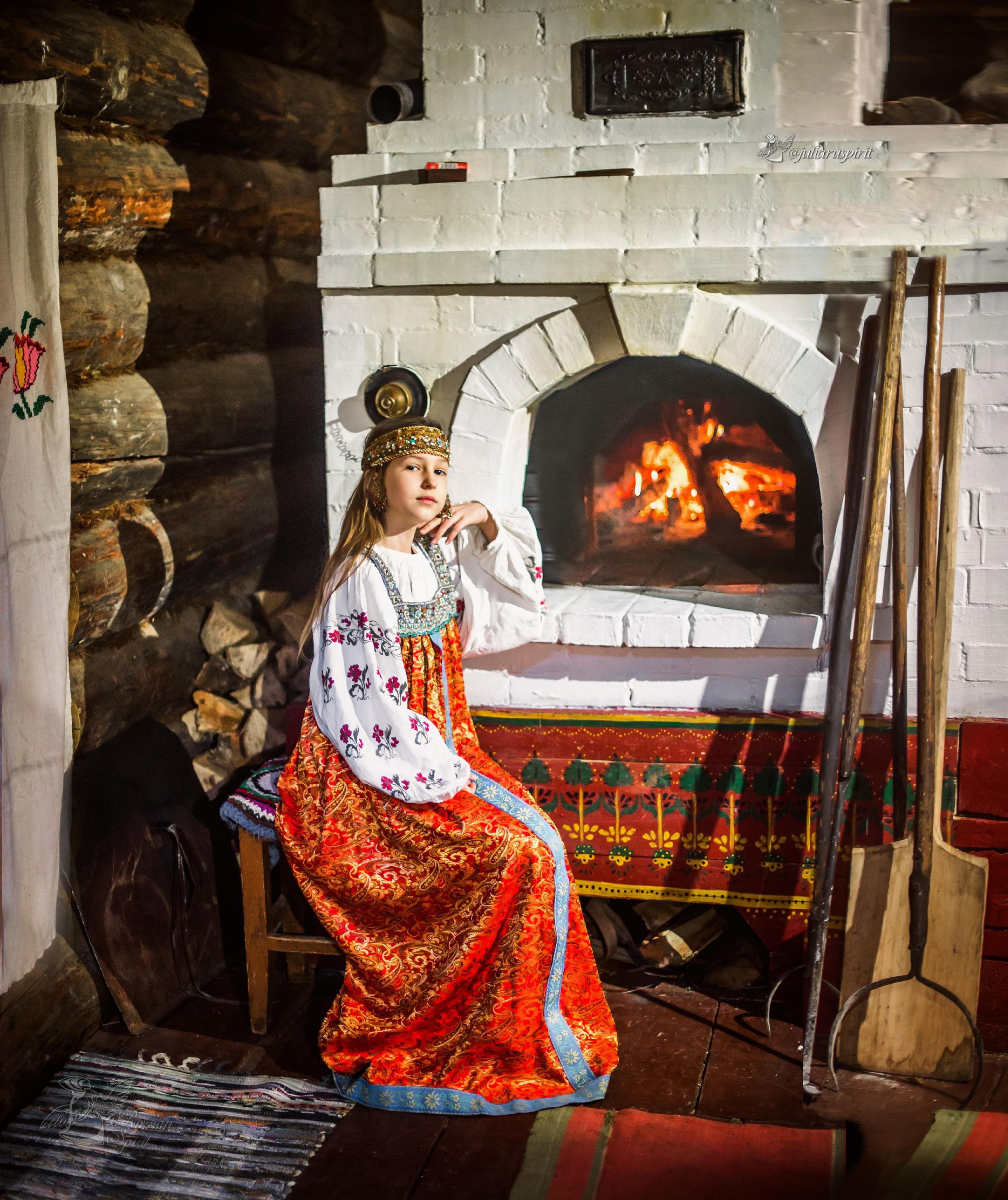 Девушка в платье в русском стиле на лавочке у настоящей русской печки