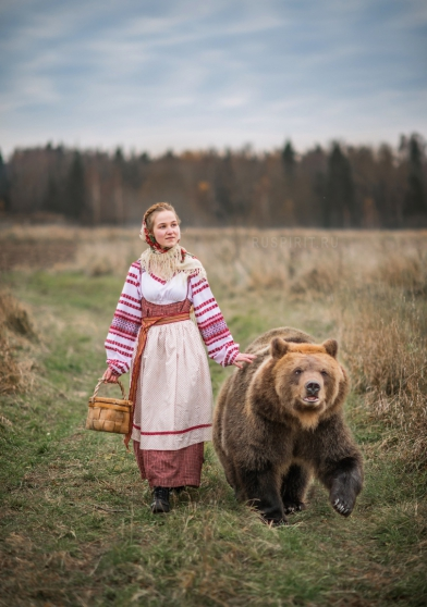 русская девушка в национальном костюме на прогулке с медведем