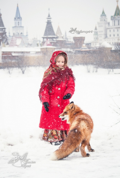 Девочка кормит лису на фоне измайловского кремля