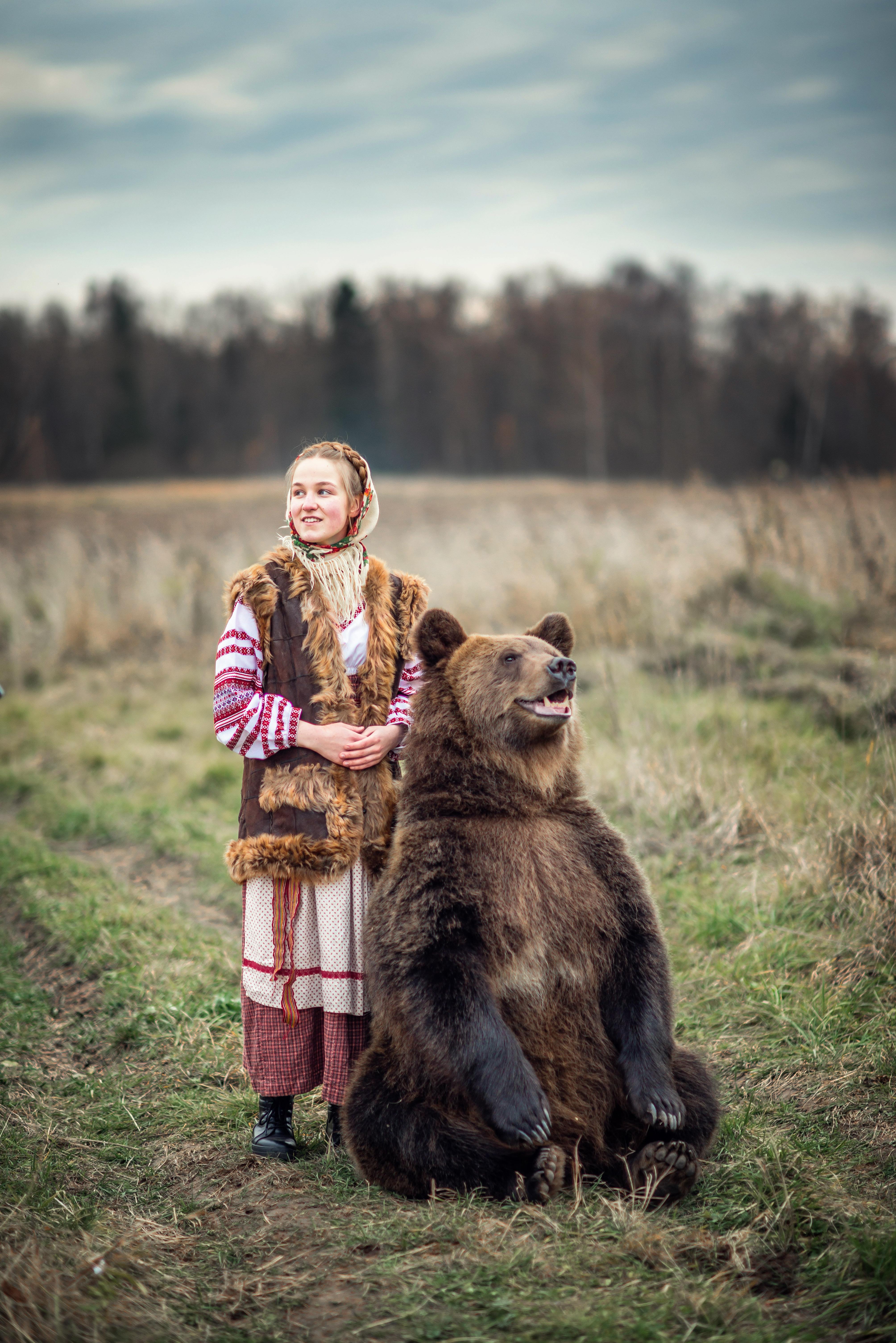Девочка в национальном русском платье в поле с медведем
